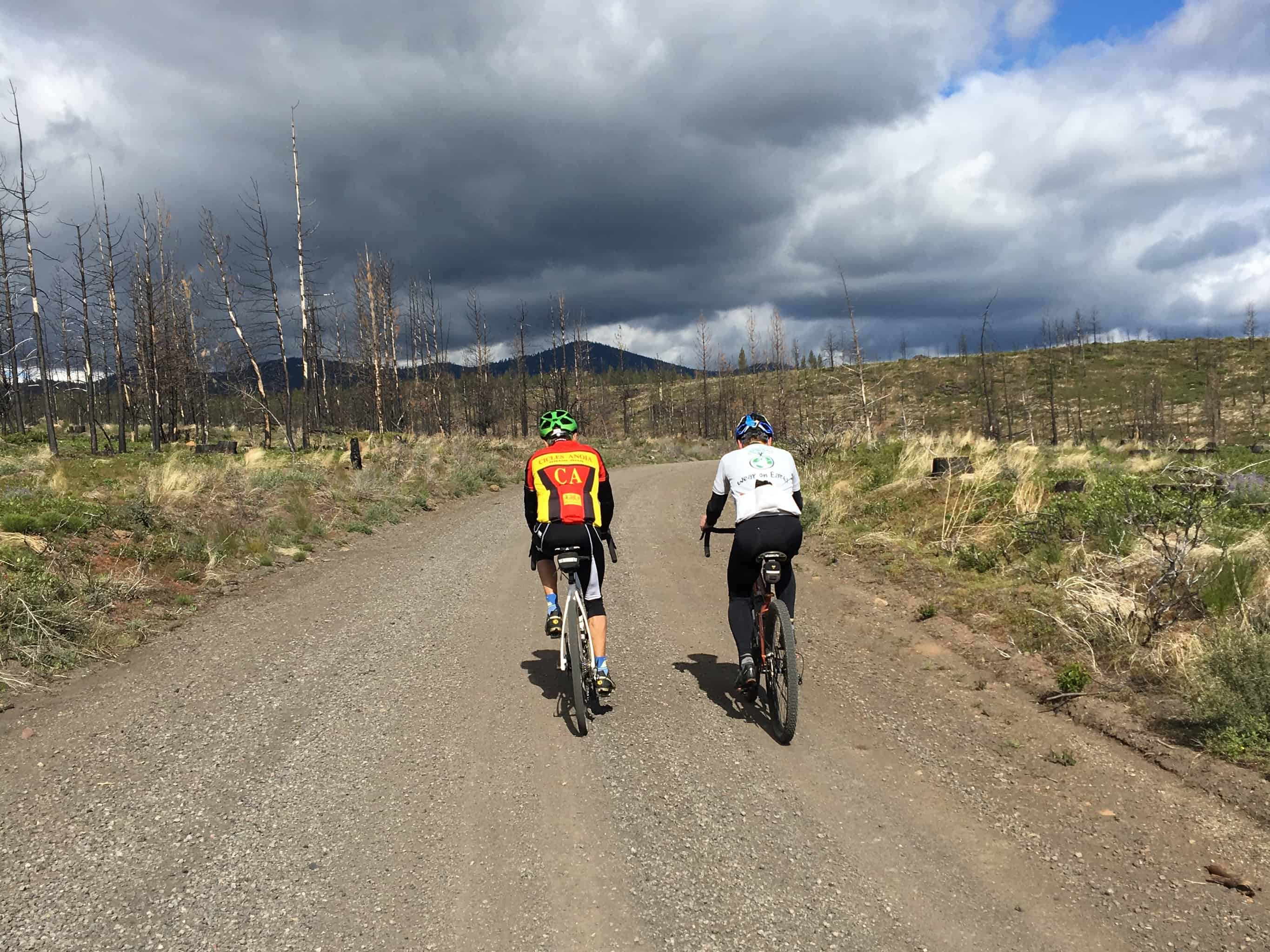 Two riders Climbing on gravel through the Two Bulls fire area, Sisters, Oregon