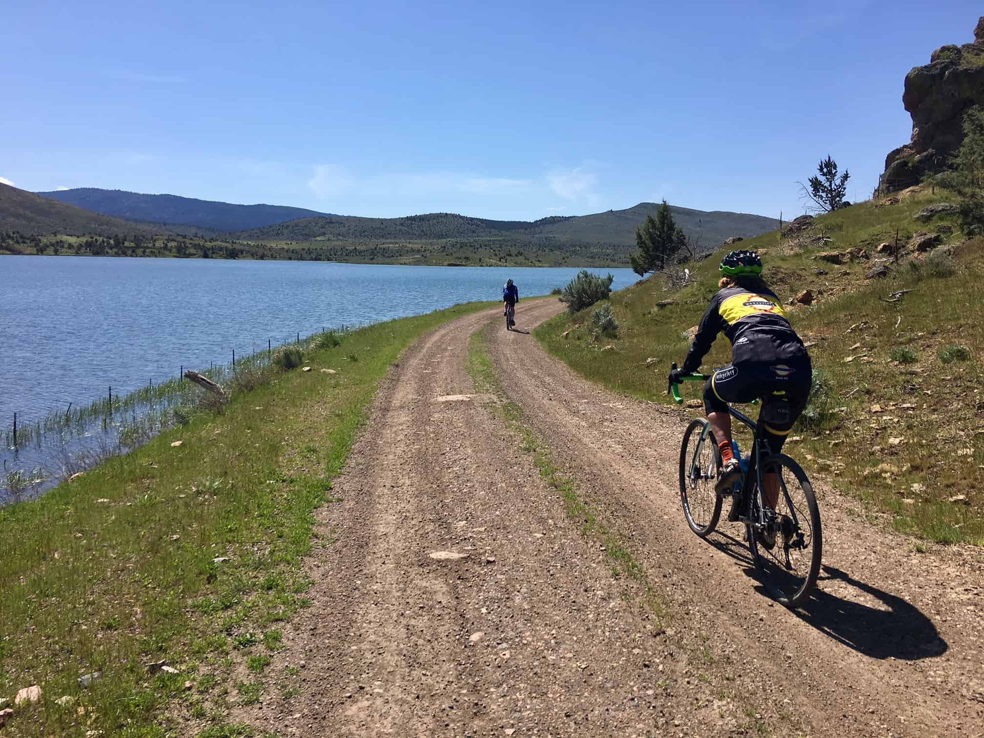 Bike riders on gravel road with Haystack reservoir to left.