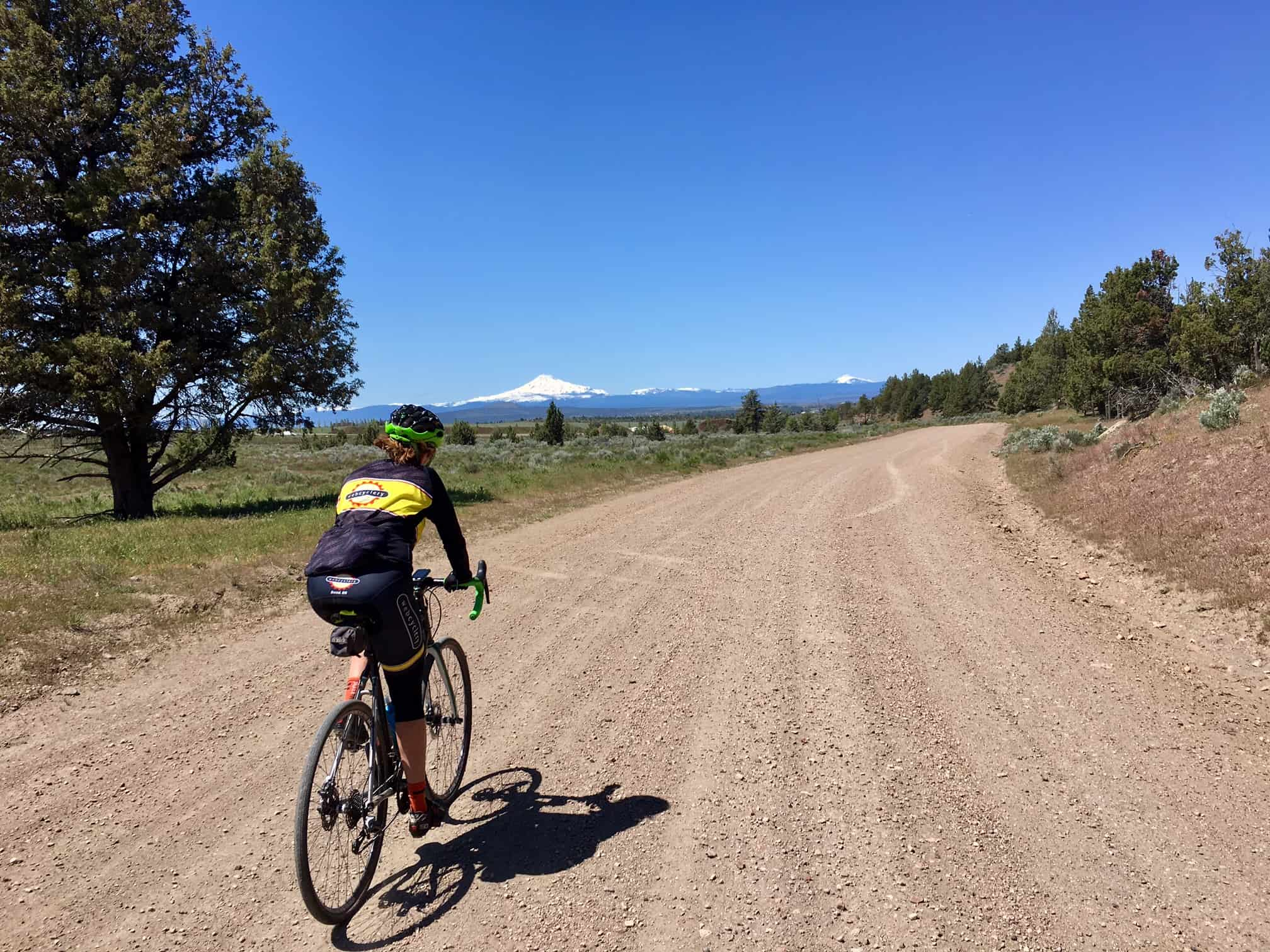 Bike rider on gravel road near Madras, Oregon with mountains in distant background.