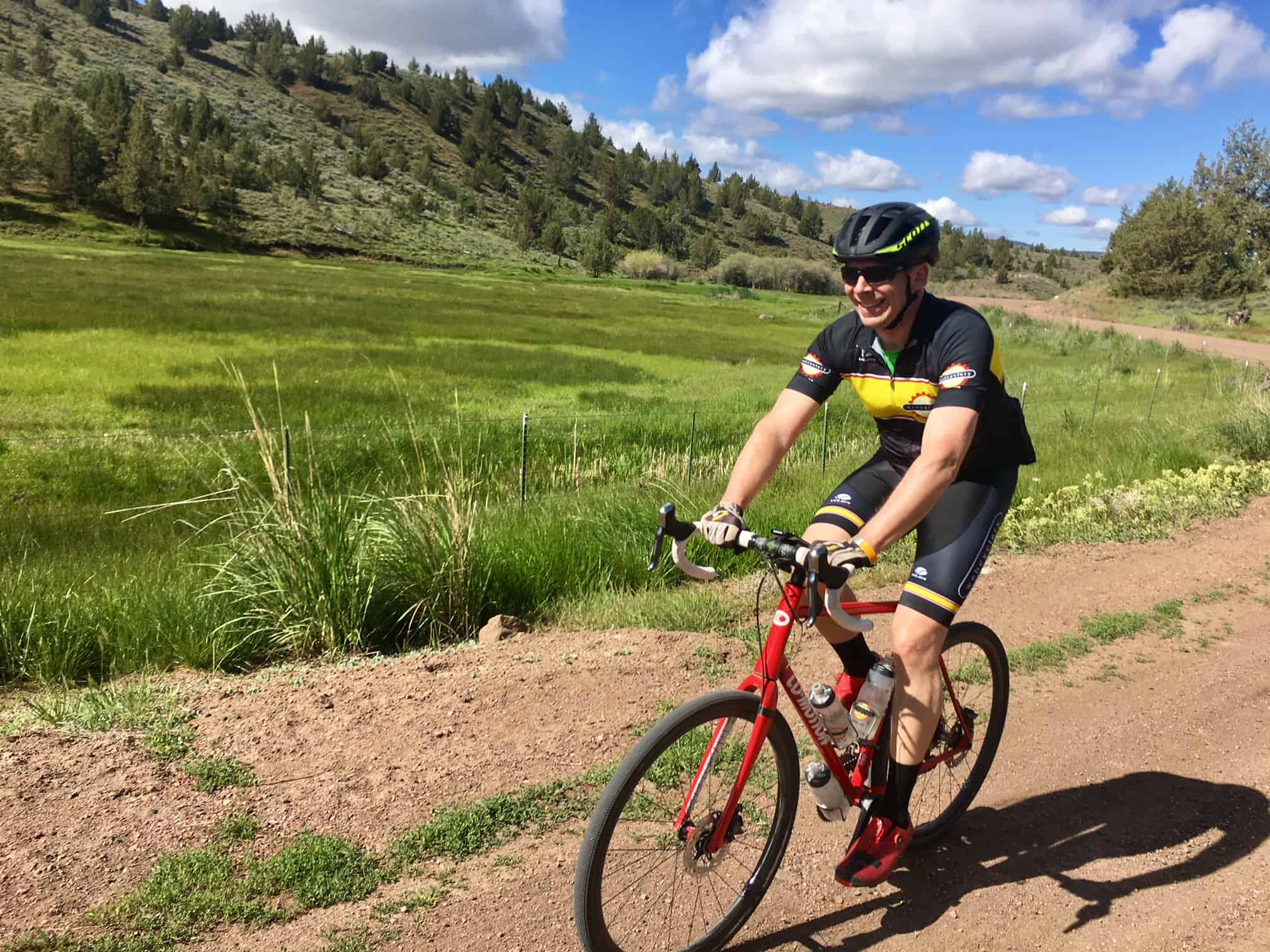 Gravel cyclist on road near Madras, Oregon with green fields in background.
