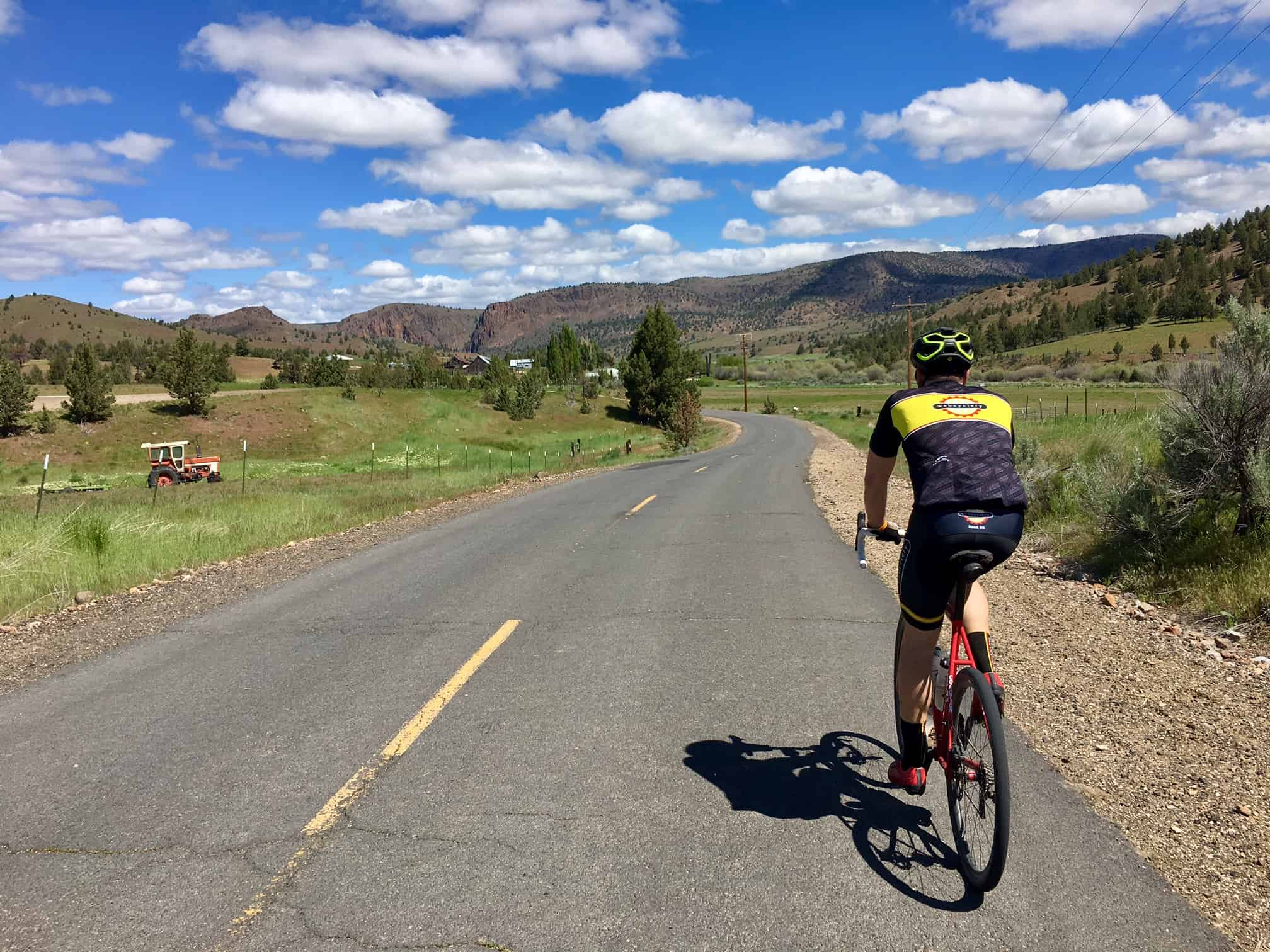 Cyclist on the paved road leading out of Ashwood, Oregon,