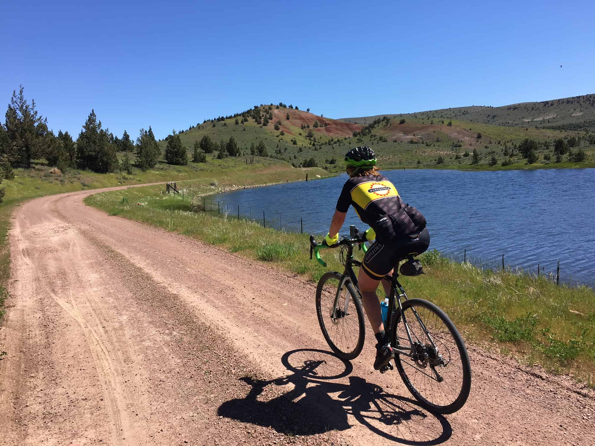 Cyclist on gravel road with Little Willow Creek reservoir in background,