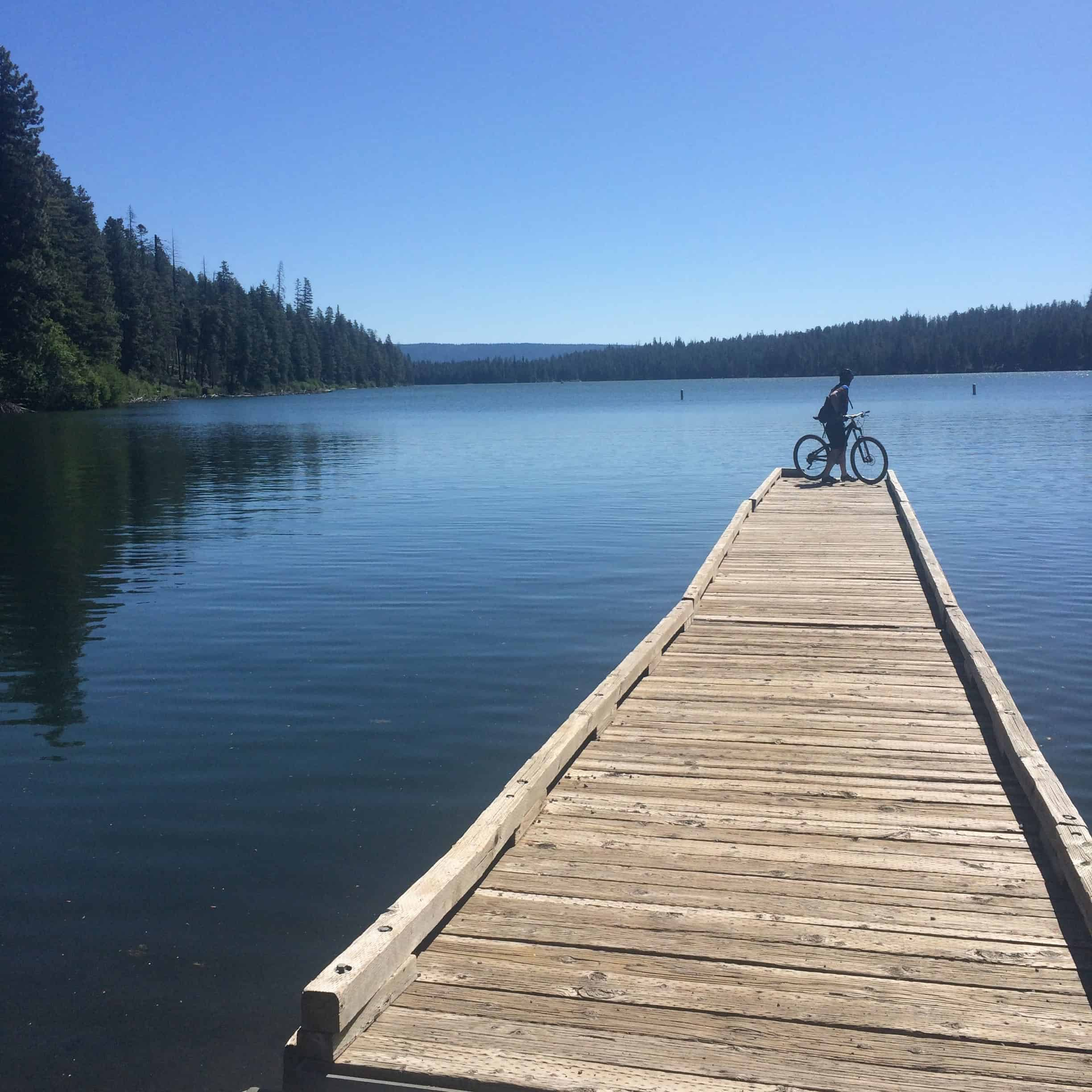 Cyclist on pier by Suttle Lake, Oregon