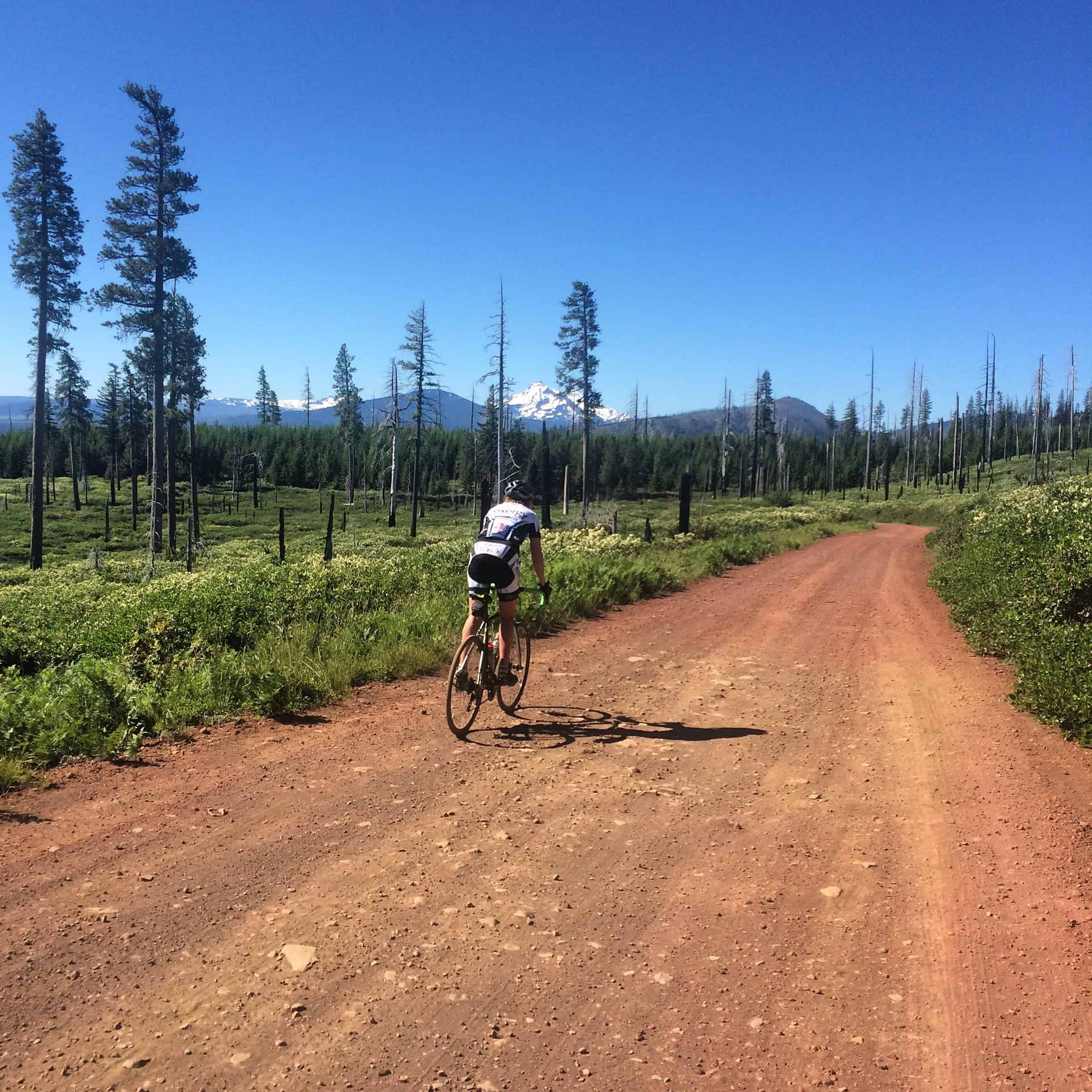 Cyclist descending gravel from Round Lake to Suttle Lake, Oregon