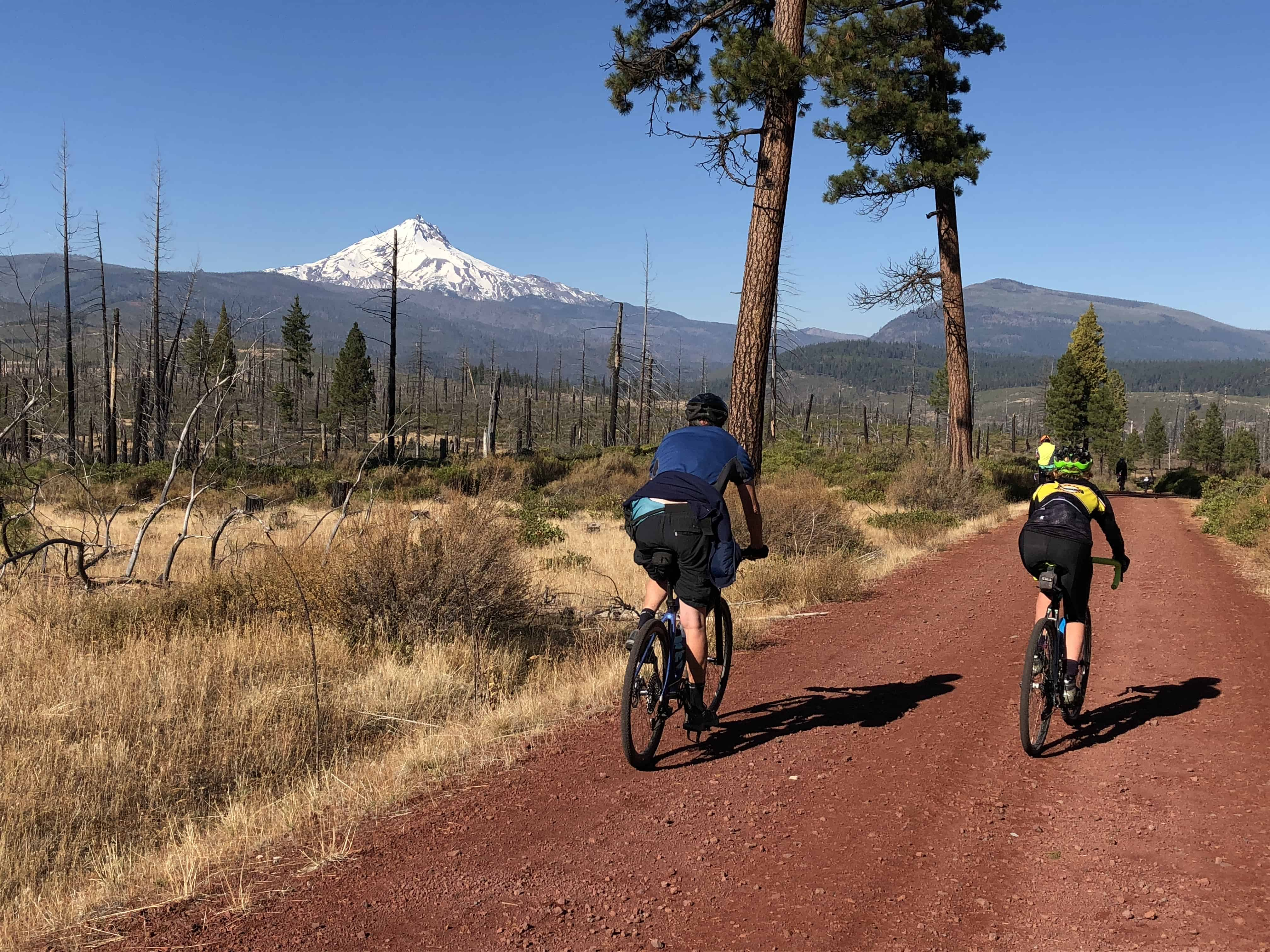 Gravel cyclists on red cinder by Mt Jefferson