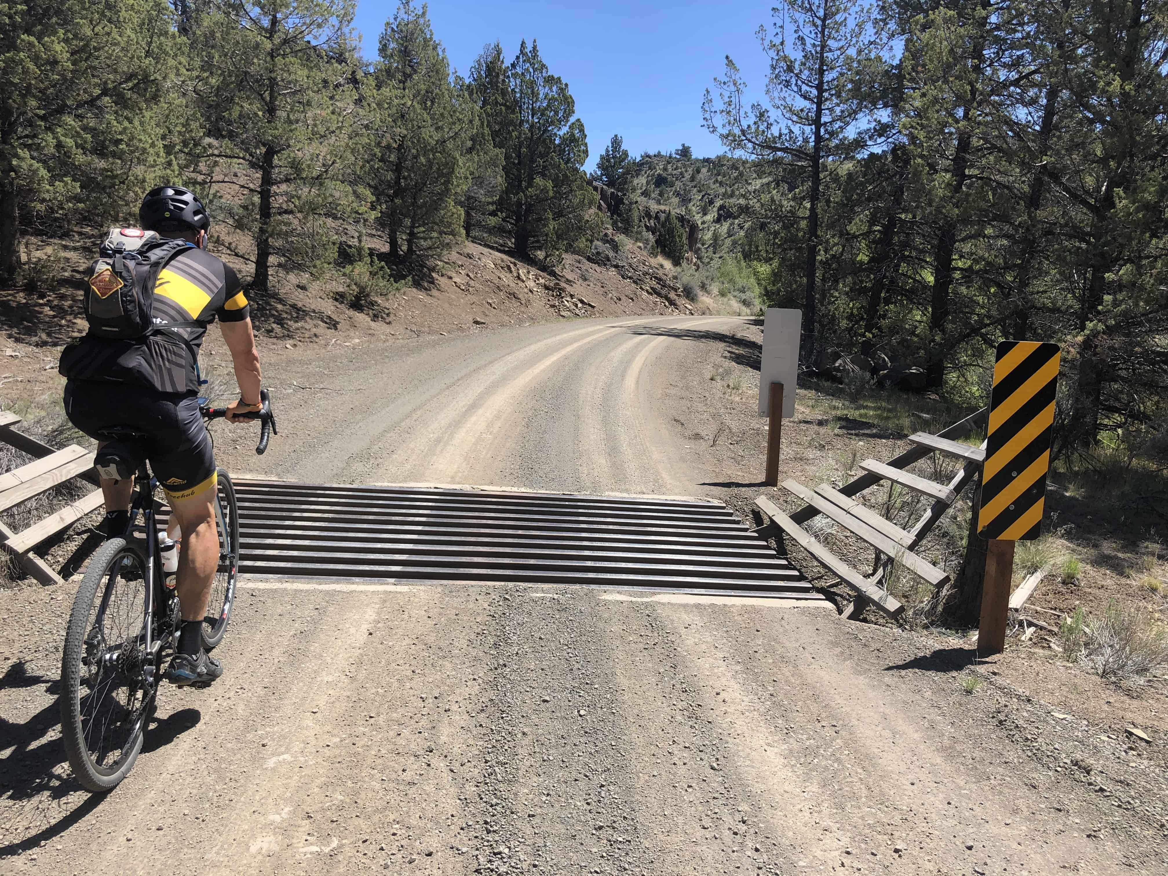Gravel cyclist crossing over a cattle guard in Central Oregon.