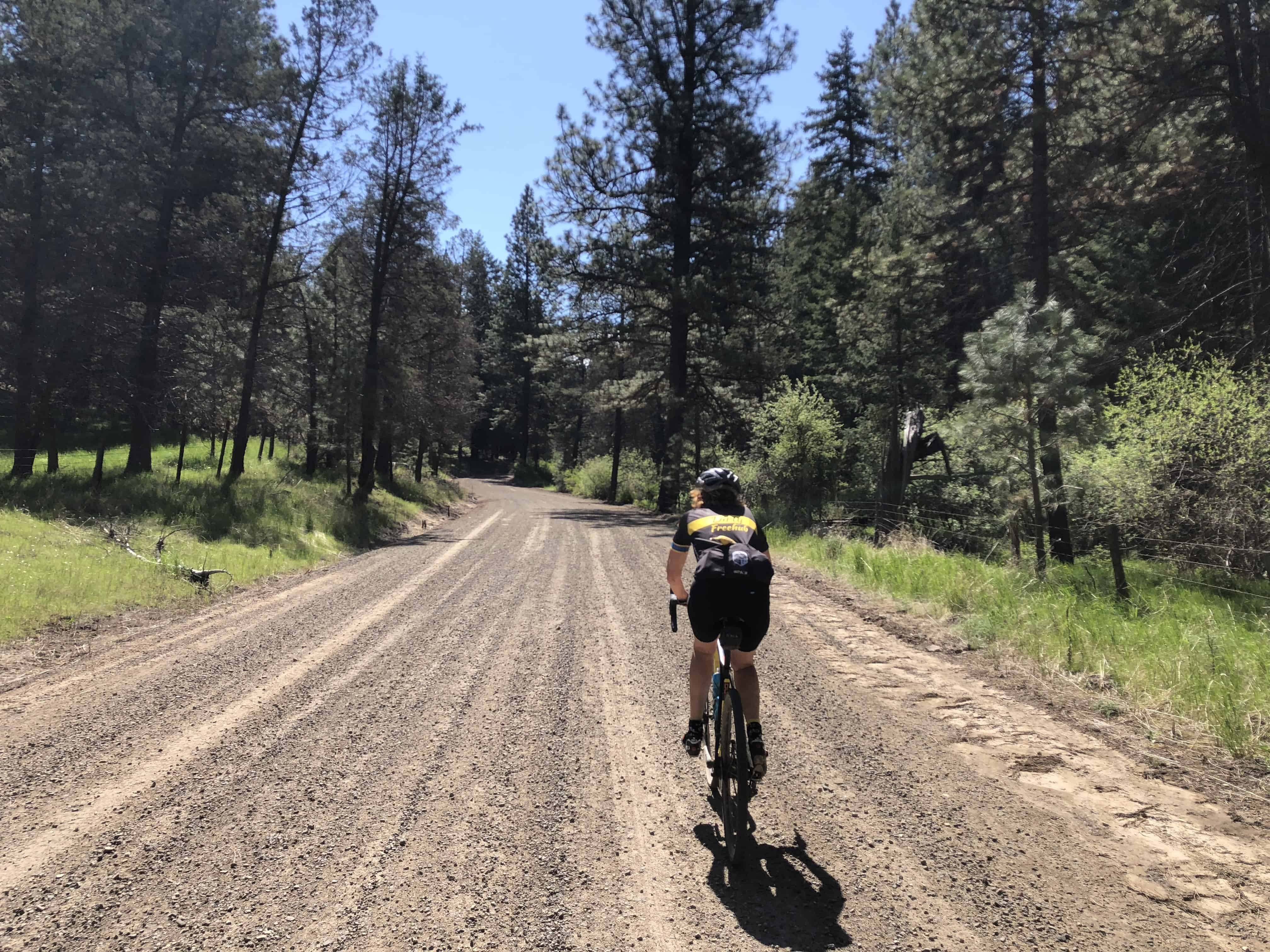 Cyclist riding gravel on Cottonwood Creek Road by Fossil, Oregon