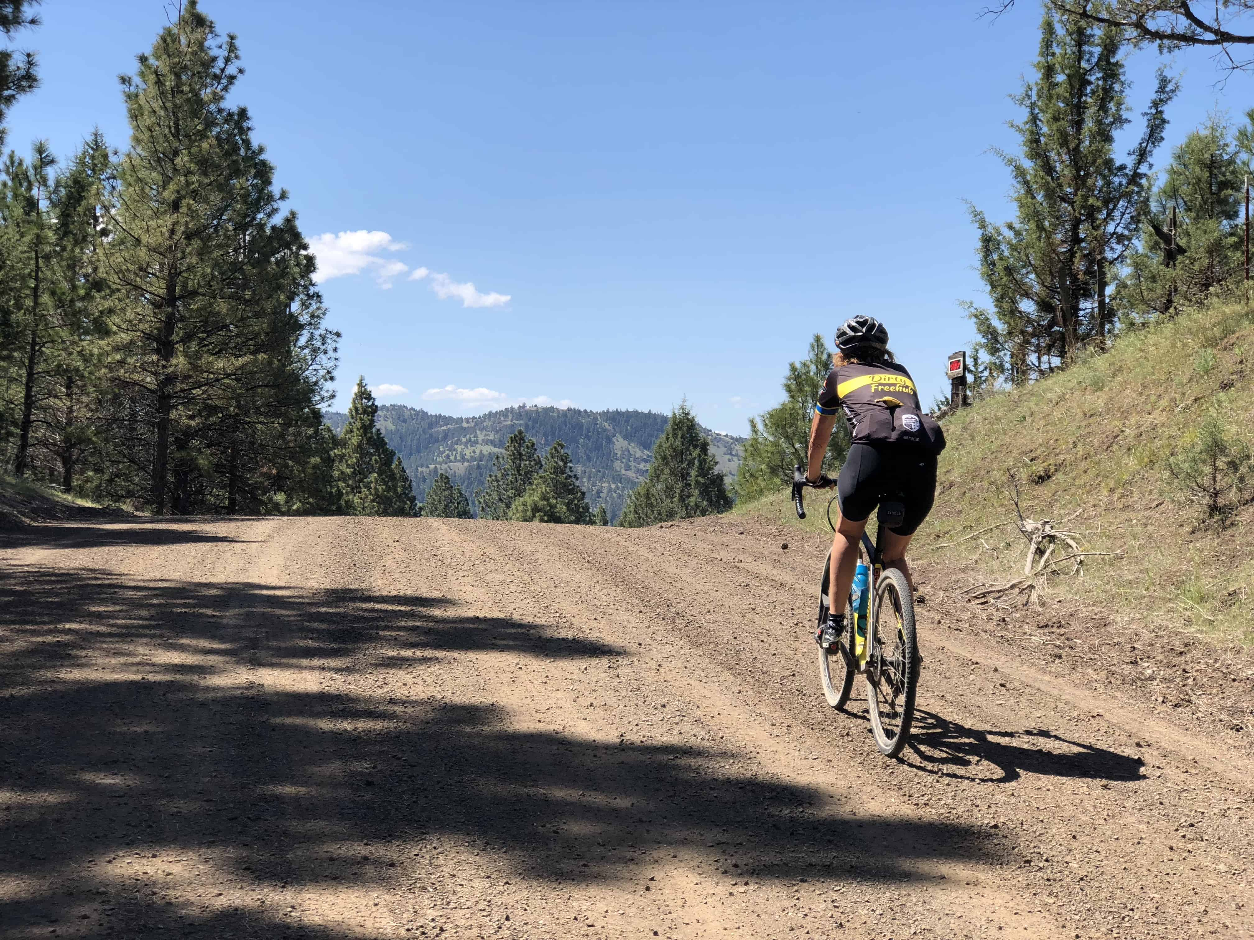 Cyclist summitting dirt section of Cottonwood Creek Road by Fossil, Oregon