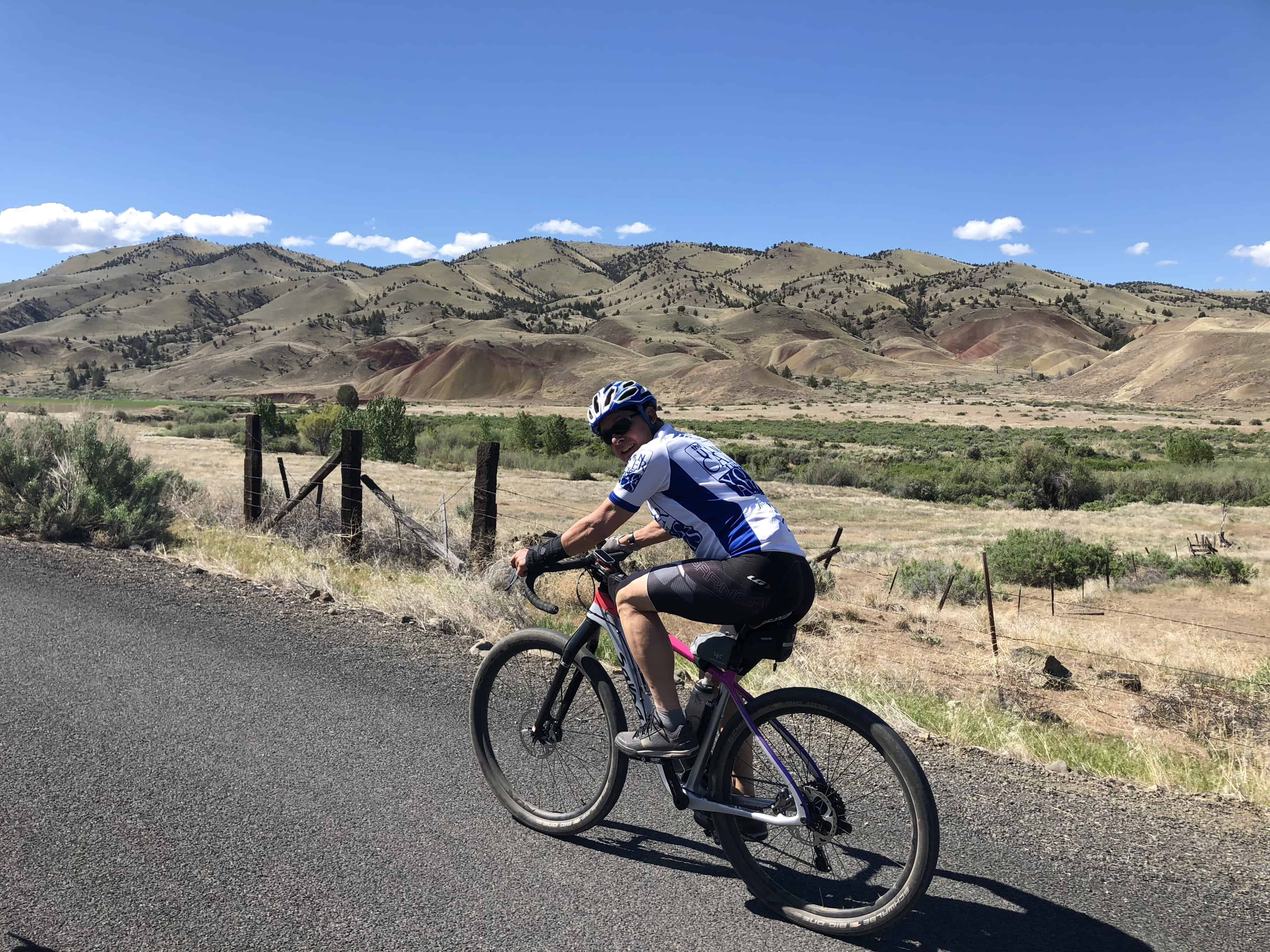 Cyclist on paved road near Painted HIlls, Oregon.