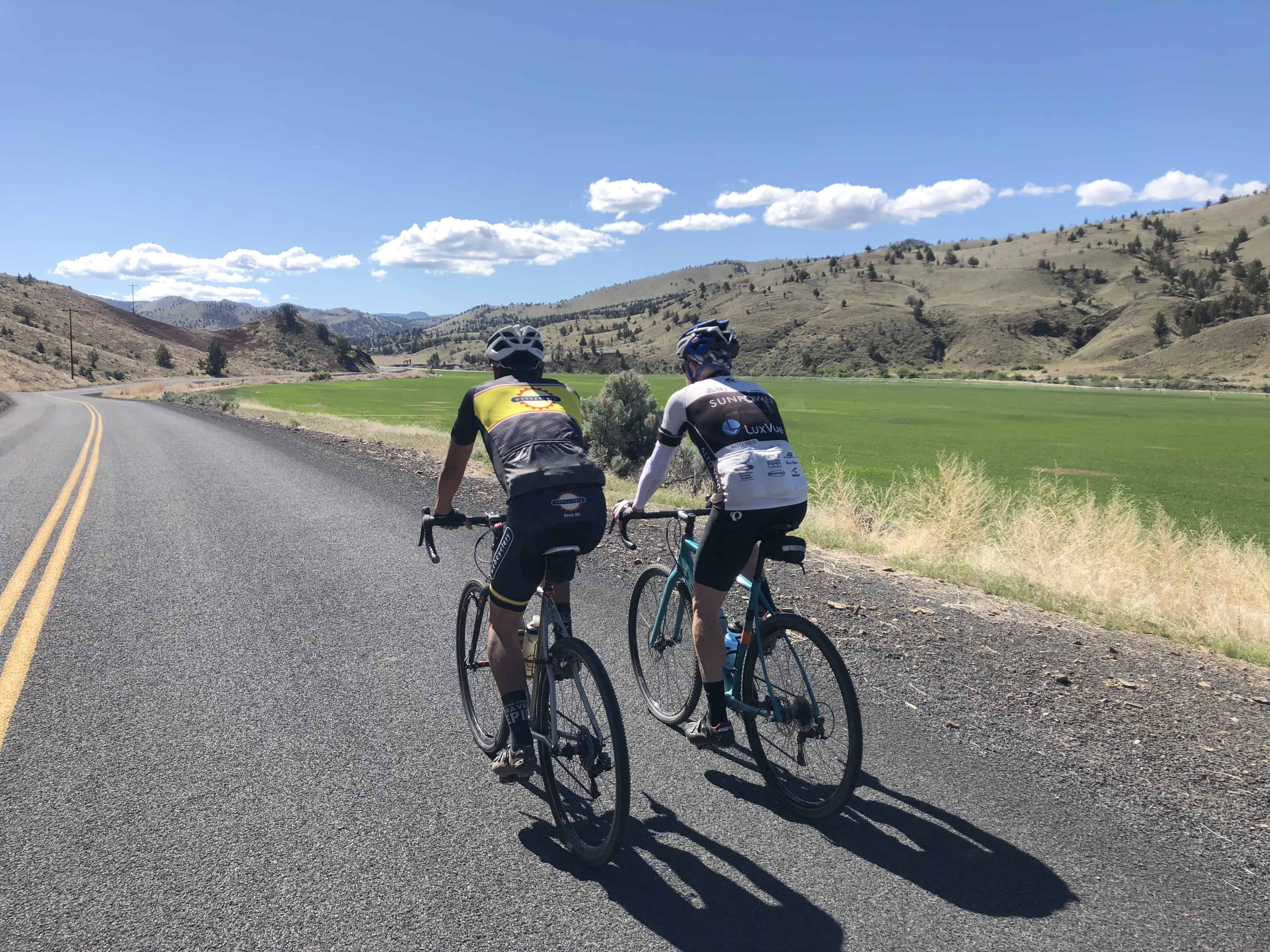 Two men cyclists on paved road near Mitchell.