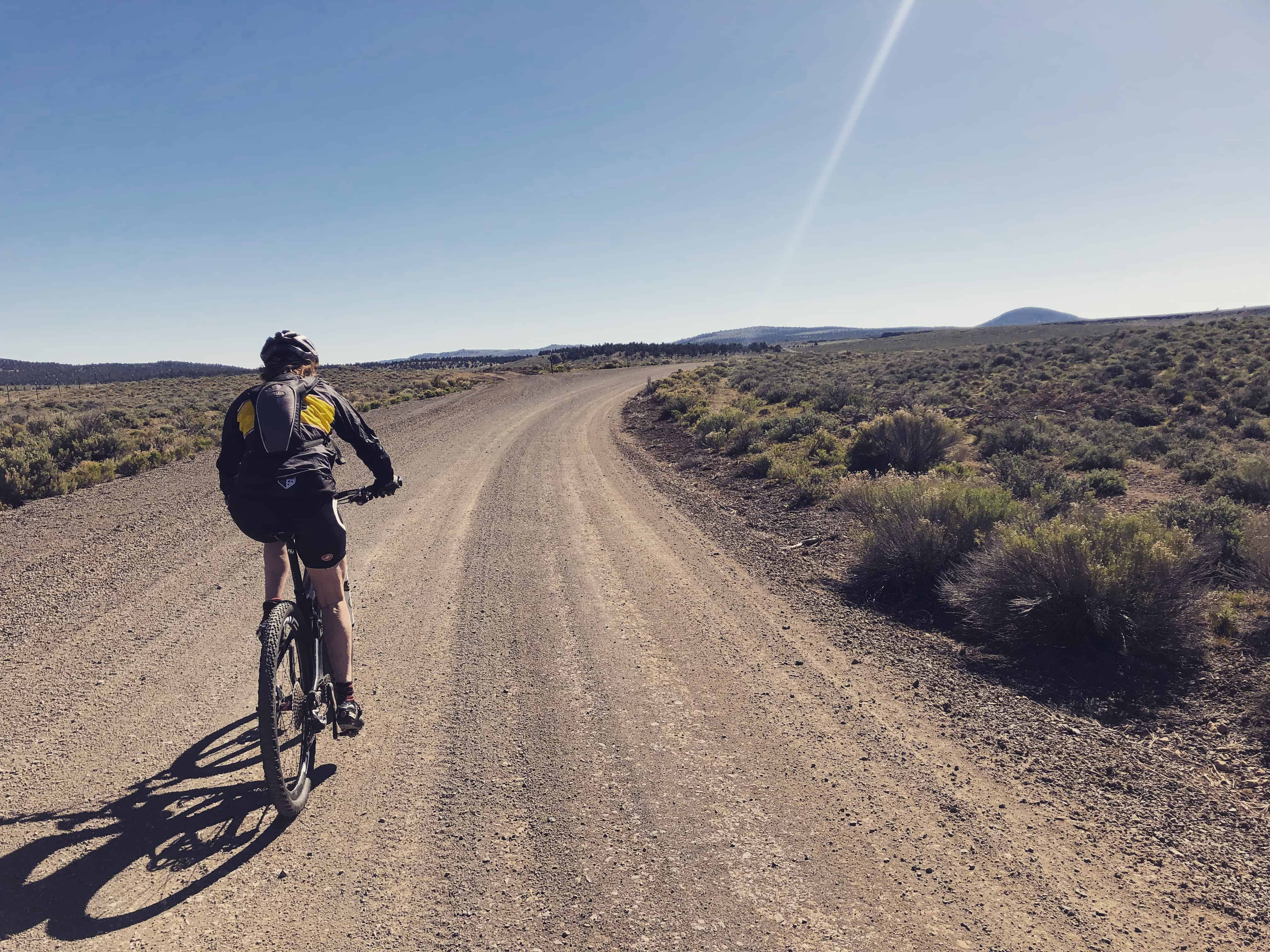 Cyclist on gravel road just outside of Brothers, Oregon.