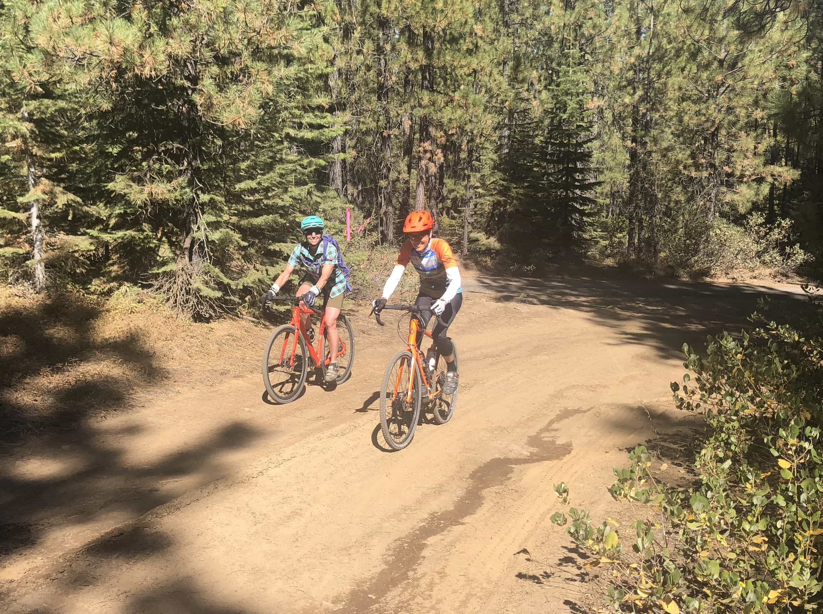 Two women gravel riders on a moon dust dirt road in the summer.