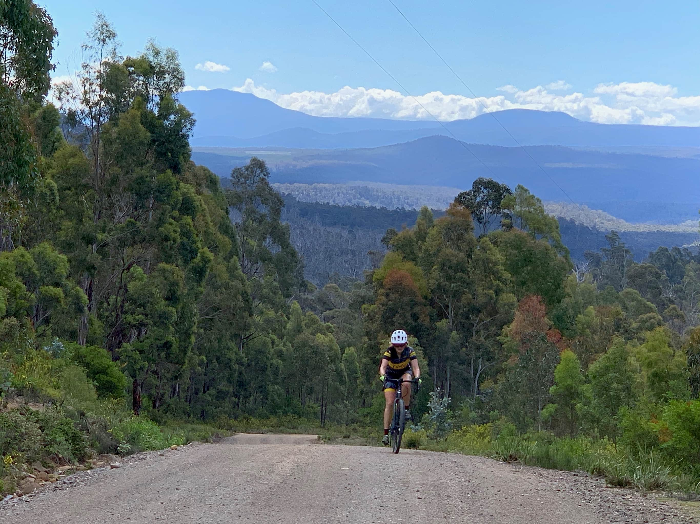 Bike rider on steep section of grave road with views far into the distance.