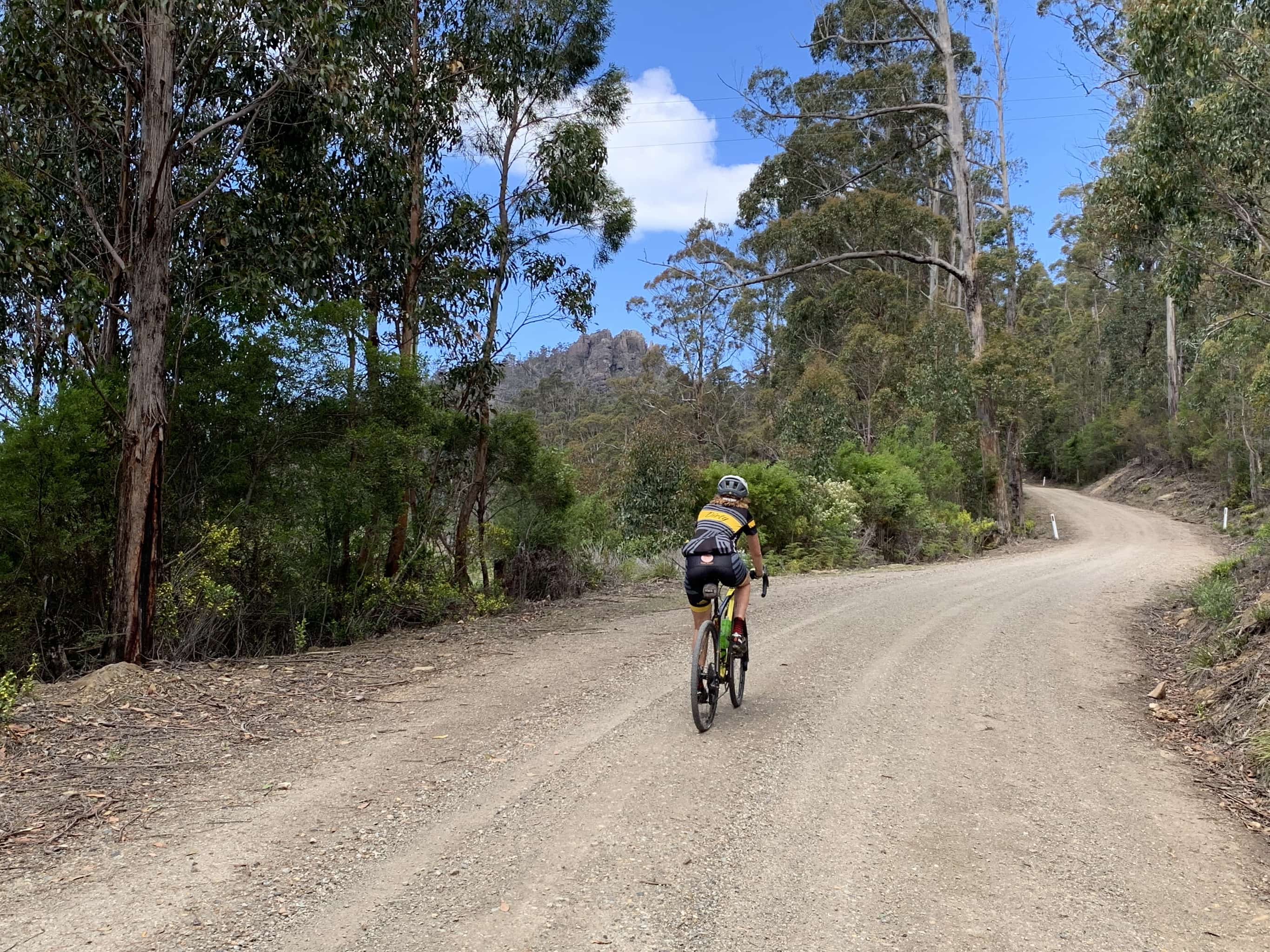 Bike rider on gravel road that winds right and then left in sweeping turns.