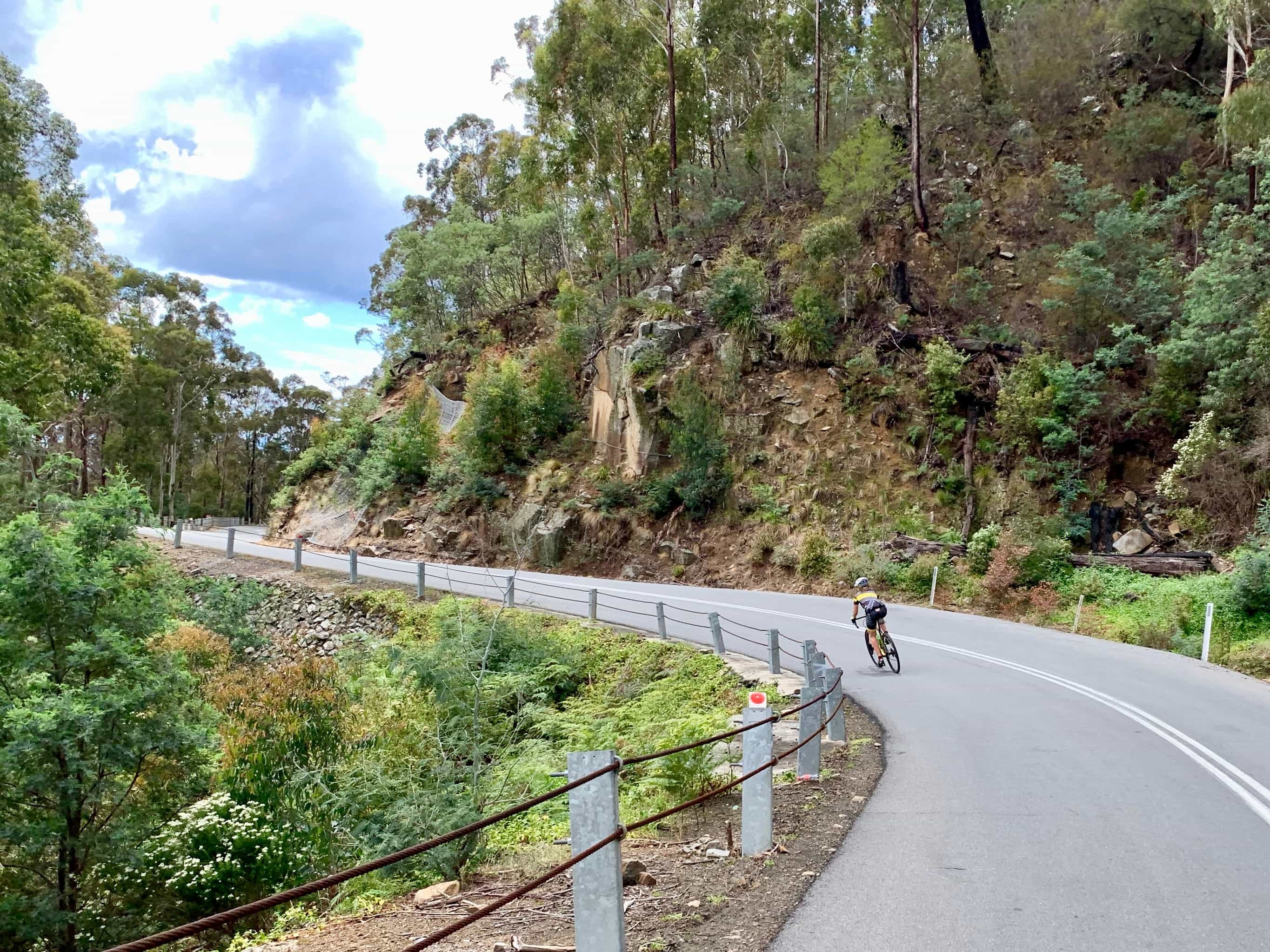 Bike rider descending St. Marys pass on paved road.