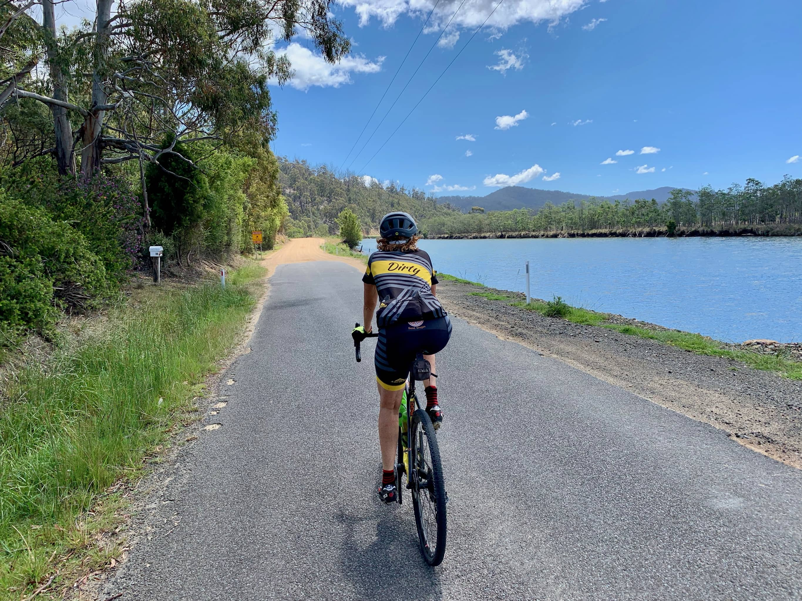Bike rider at the transition of paved road to gravel road with Scamander river to the right.
