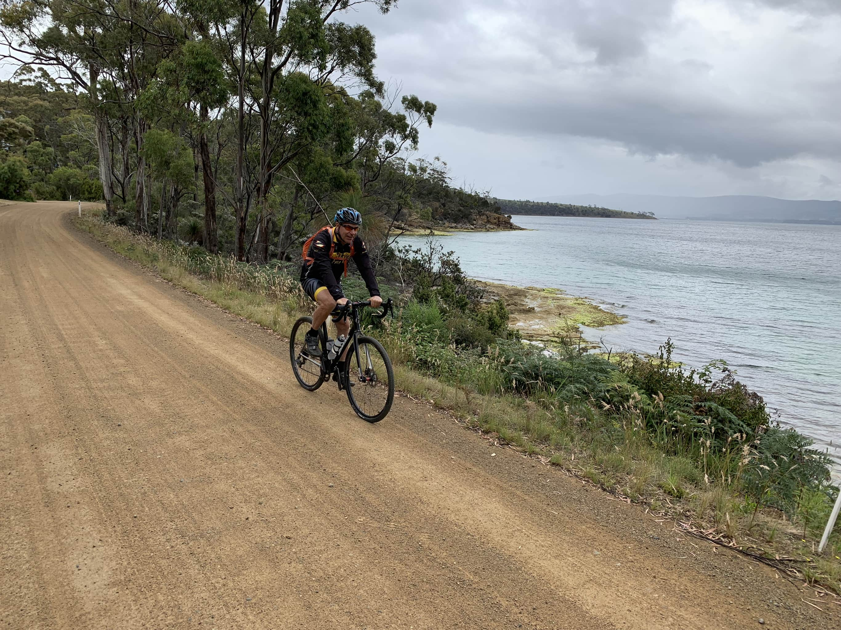Bike rider on gravel road near Dennes Point on North Bruny Island. Coast line to left.