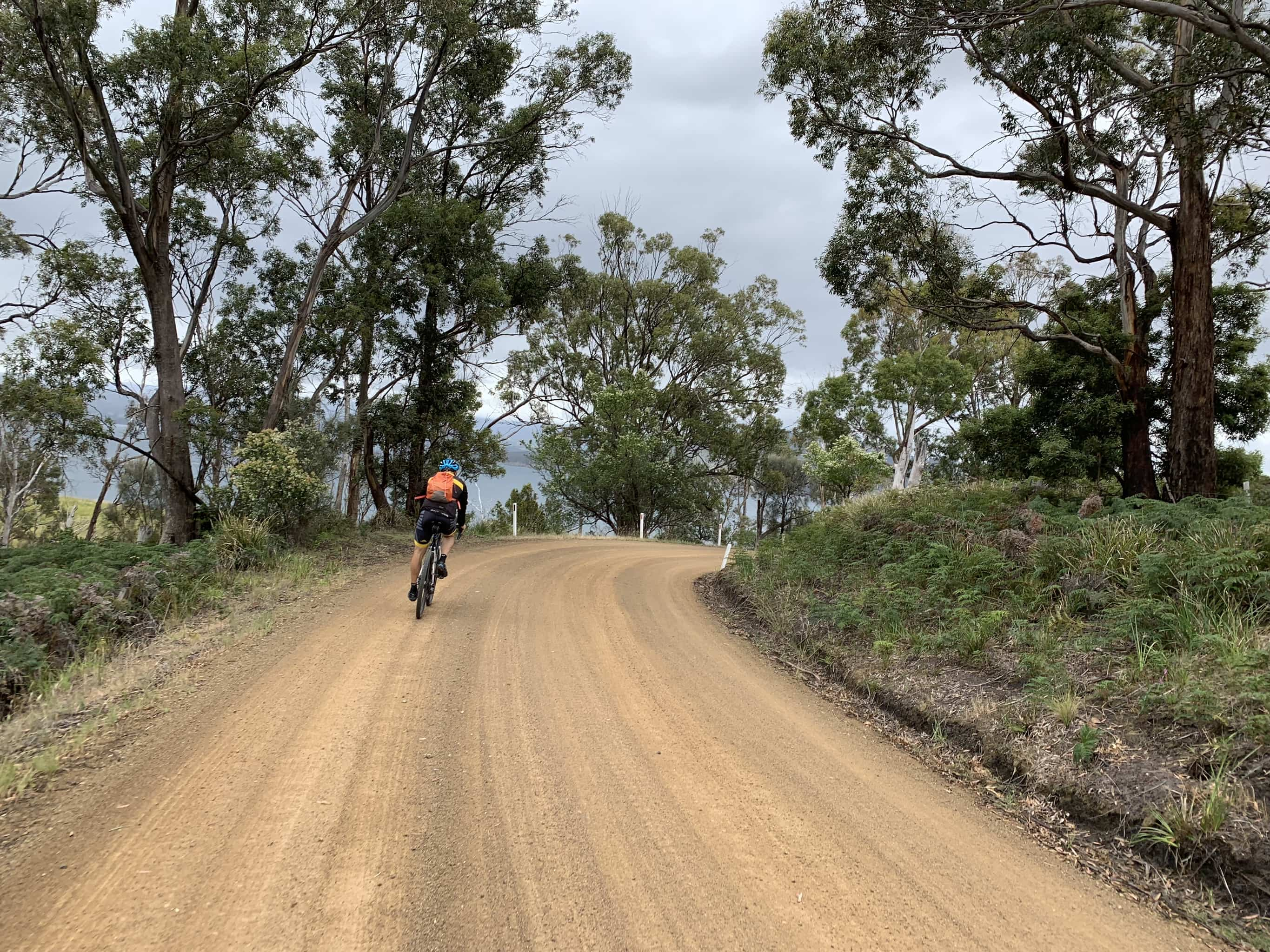 Bike rider on gravel road near Dennes Point on North Bruny Island. Coast in distance.