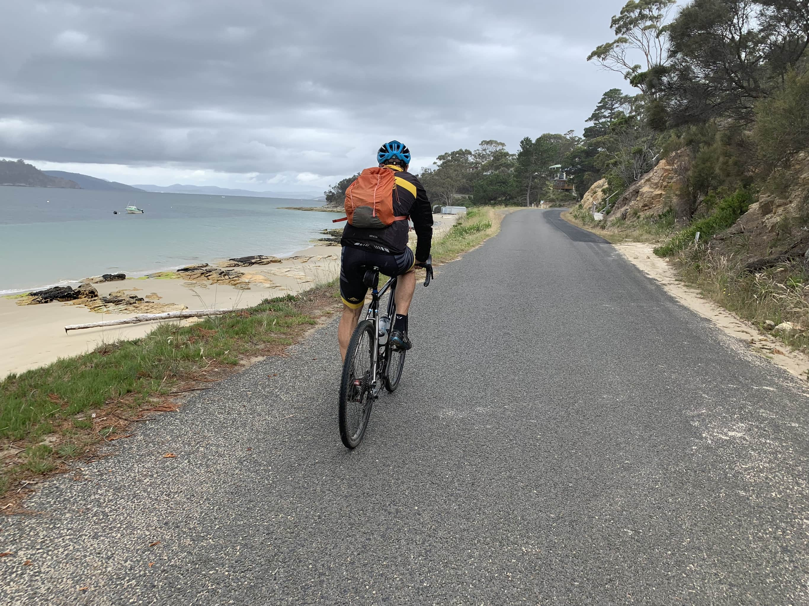 Bike rider on paved road near Dennes Point on North Bruny Island. Coast line to left.