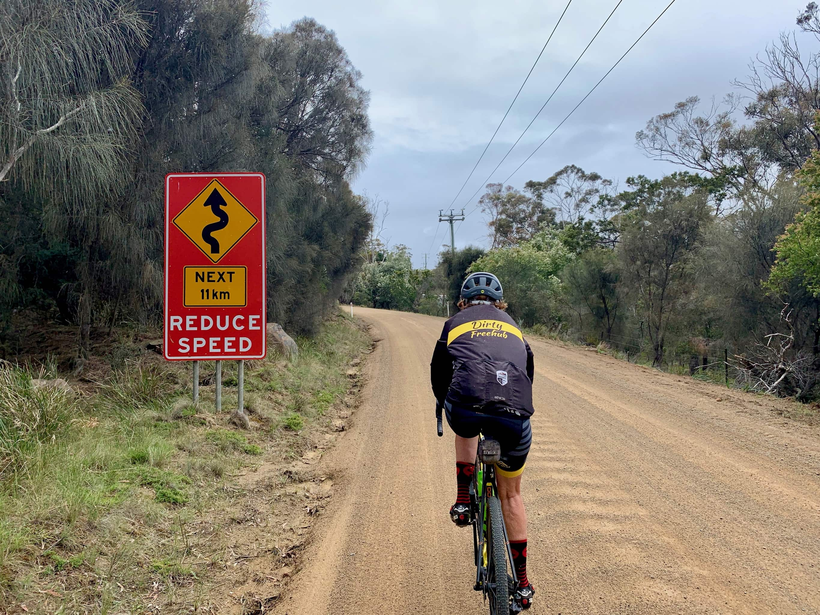 Bike rider on gravel road with road sign that cautions winding road.