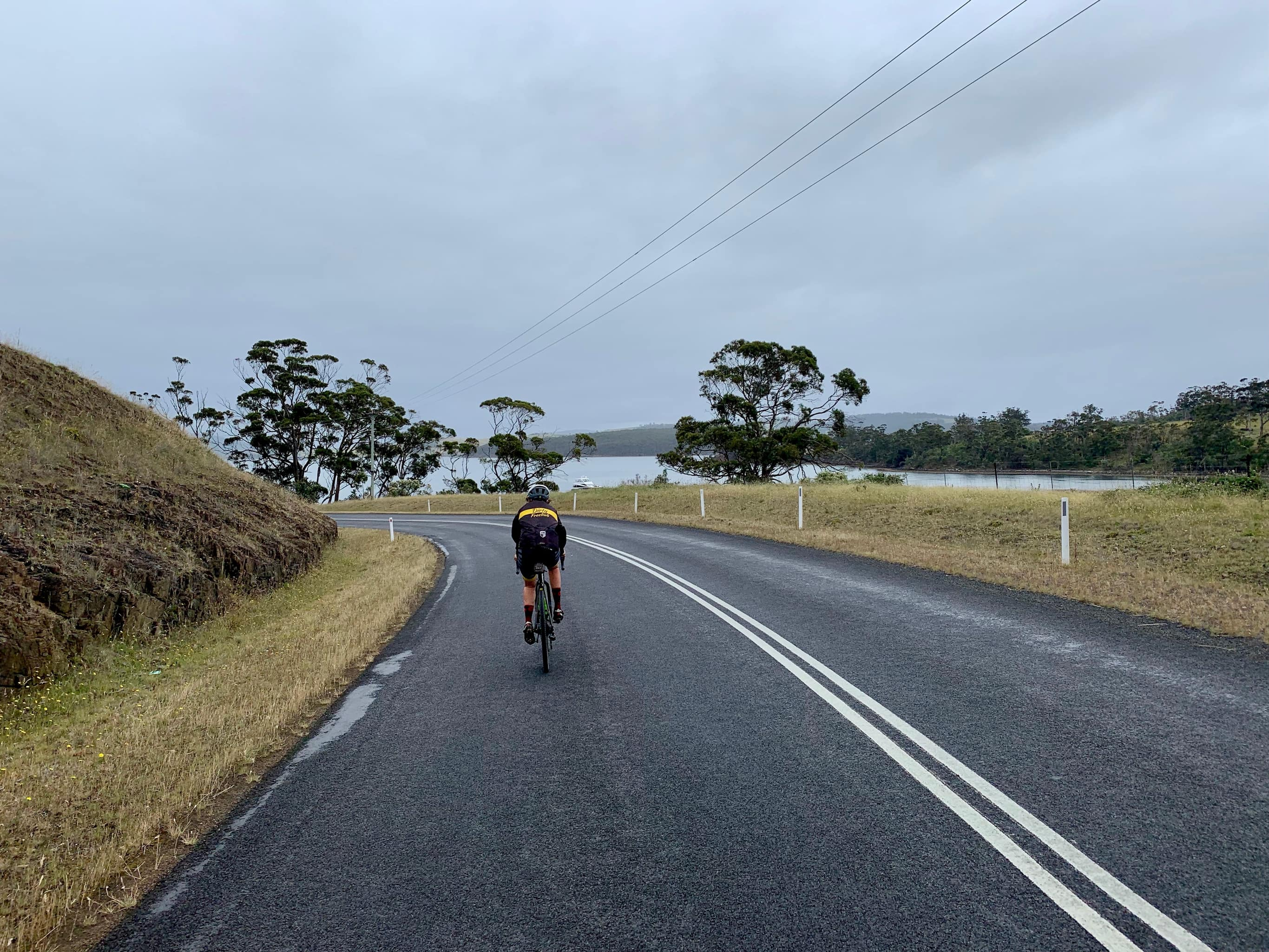 Bike rider on paved road on North Bruny Island with Barnes Bay in the far distance.