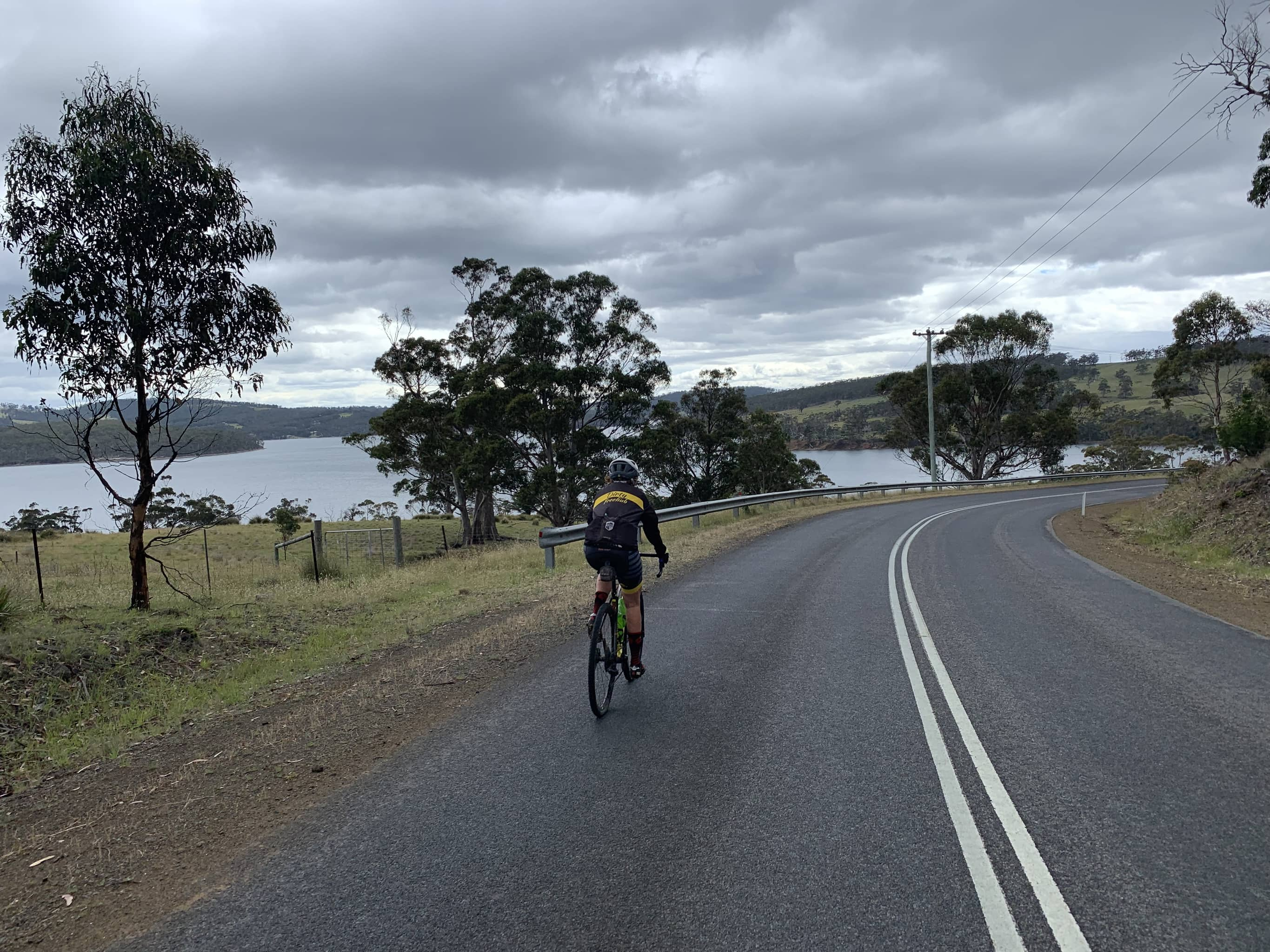 Bike rider on paved road with Barnes Bay of Bruny Island in background.