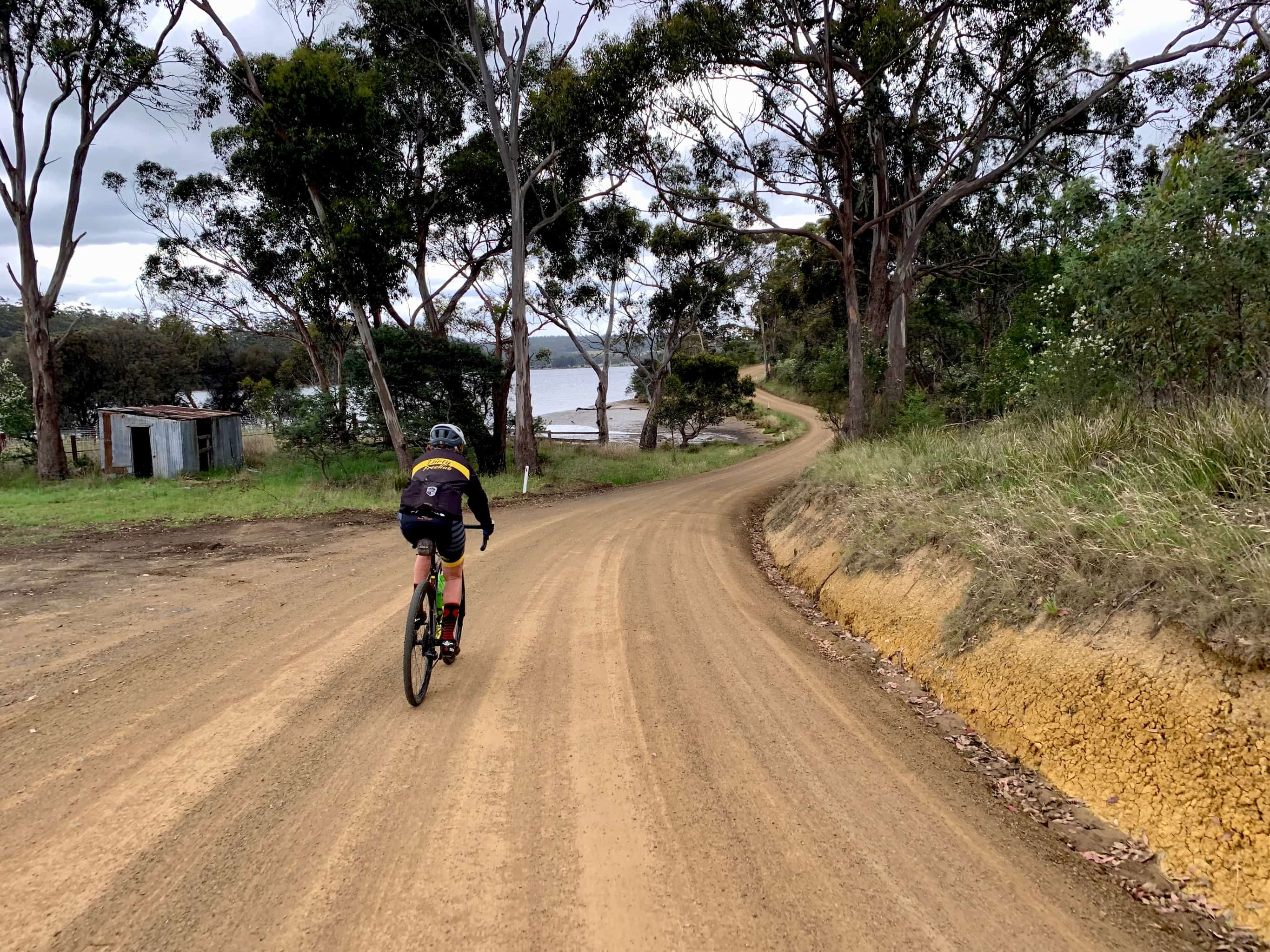 Bike rider on gravel road with Barnes Bay of Bruny Island in the distance.