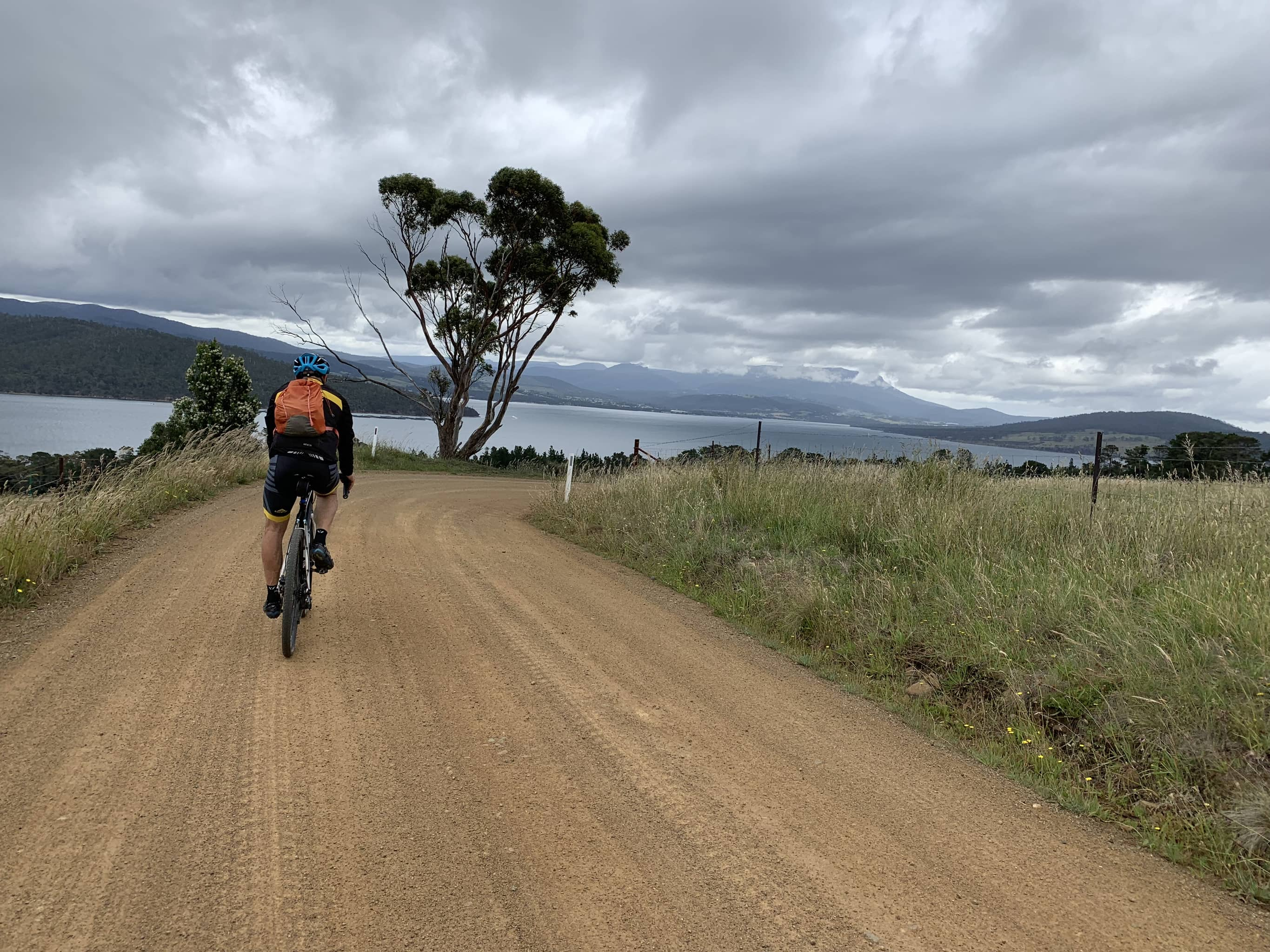 Bike rider on gravel road with ocean bay and Mt. Wellington in distance.