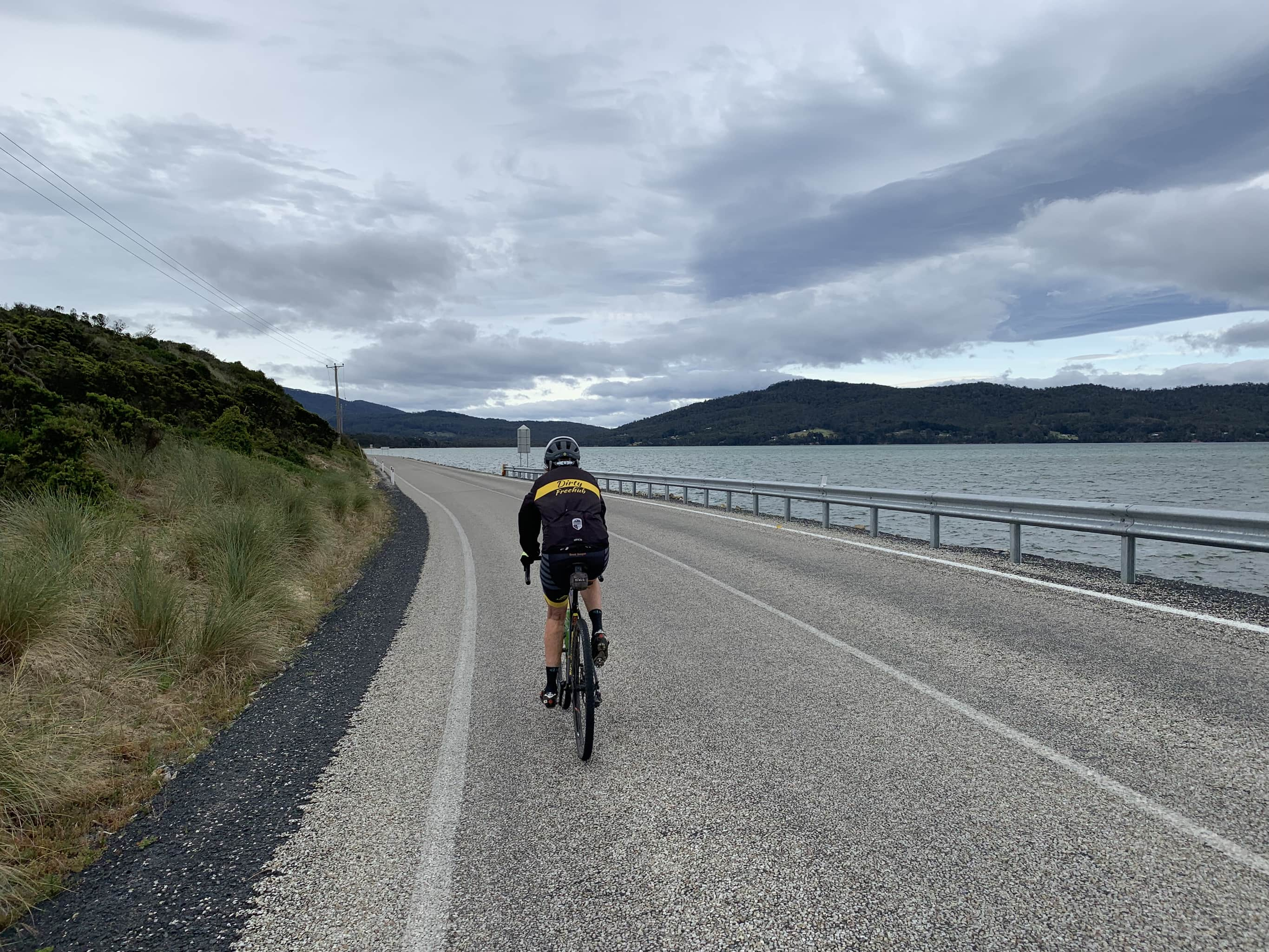 Bike rider on paved road leading south from Bruny Island Neck.