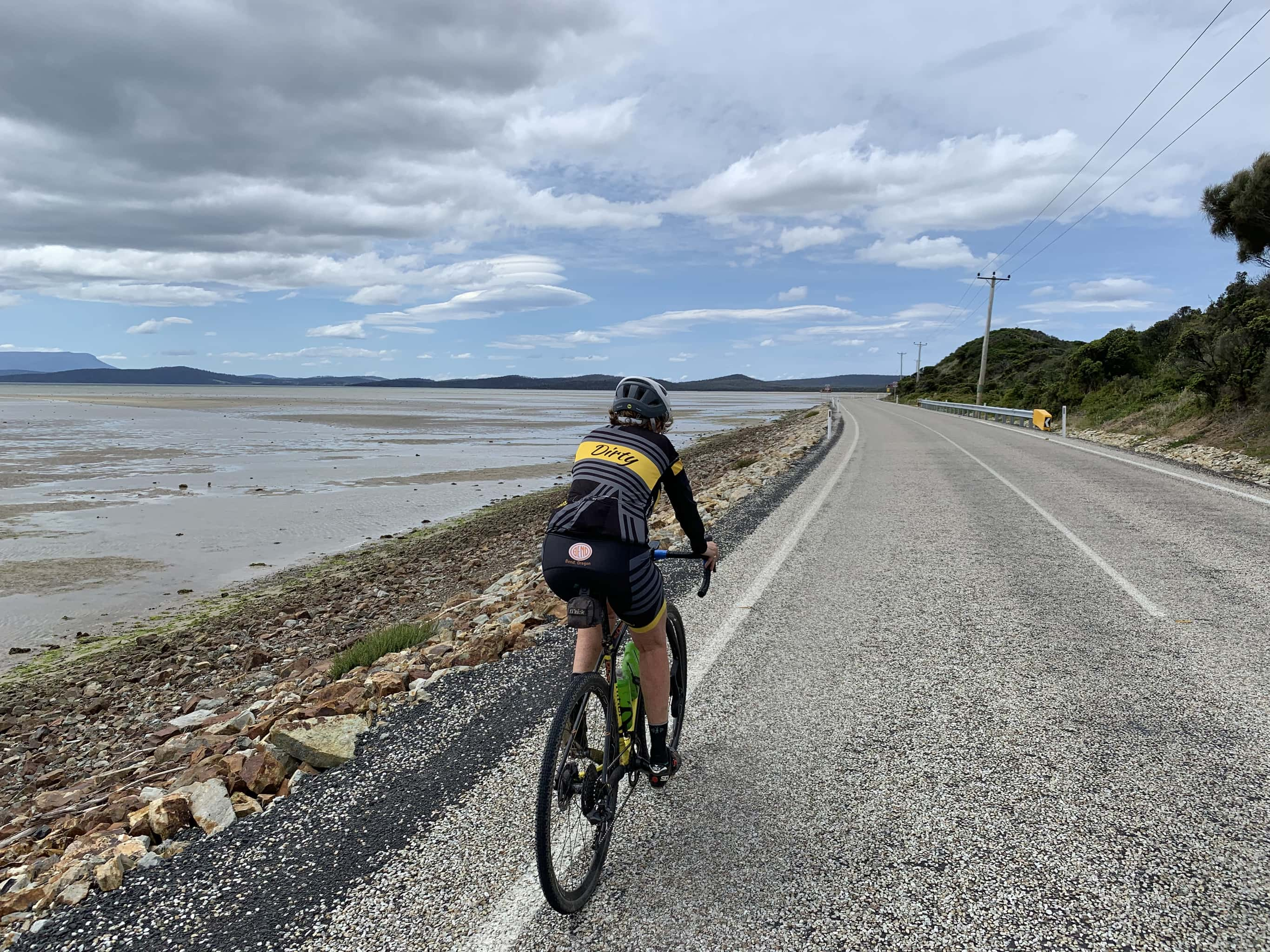 Bike rider on paved road riding towards Bruny Island Neck lookout.