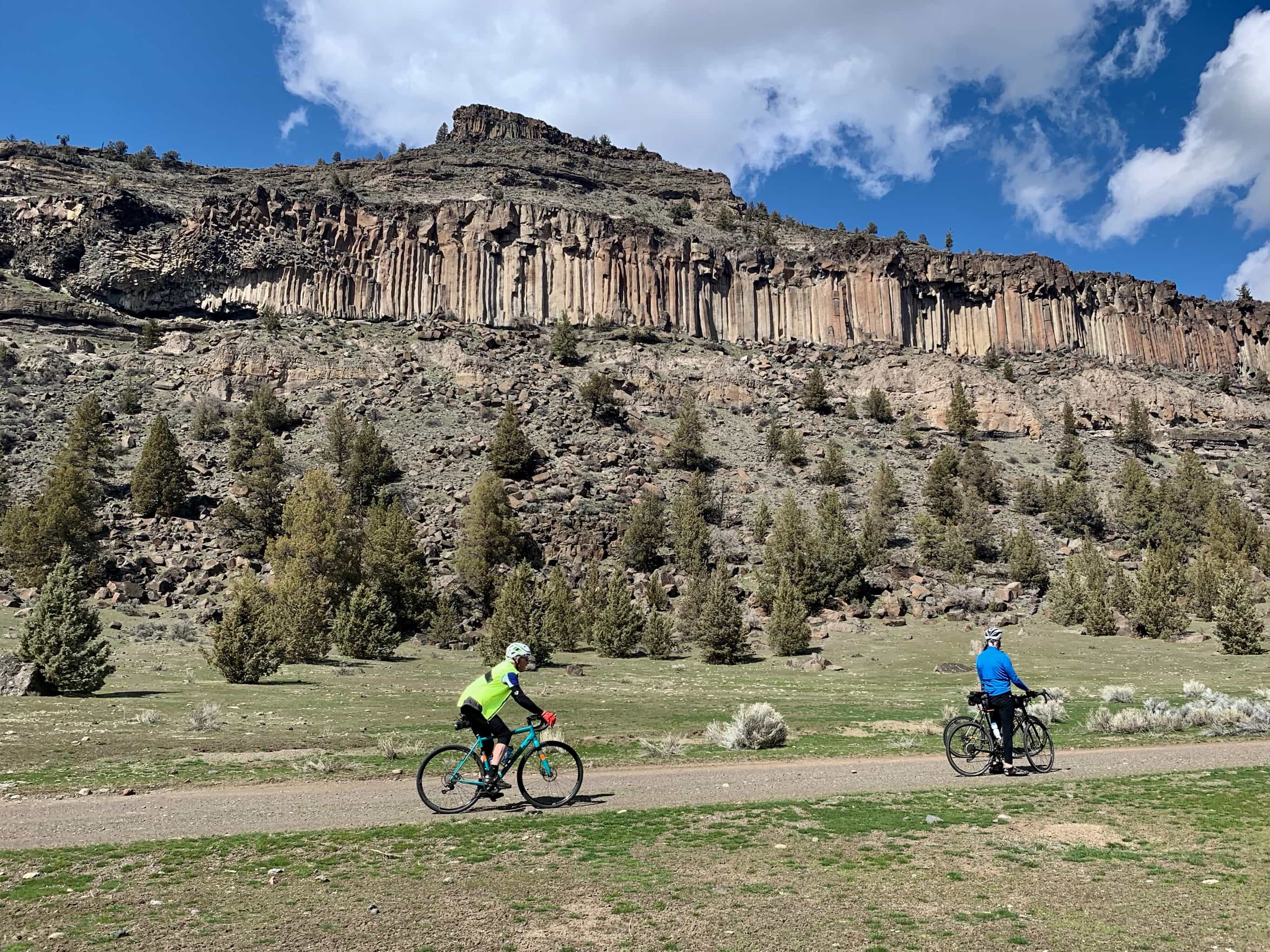 Cyclists on gravel road with basalt cliffs in background near Lake Simtustus.