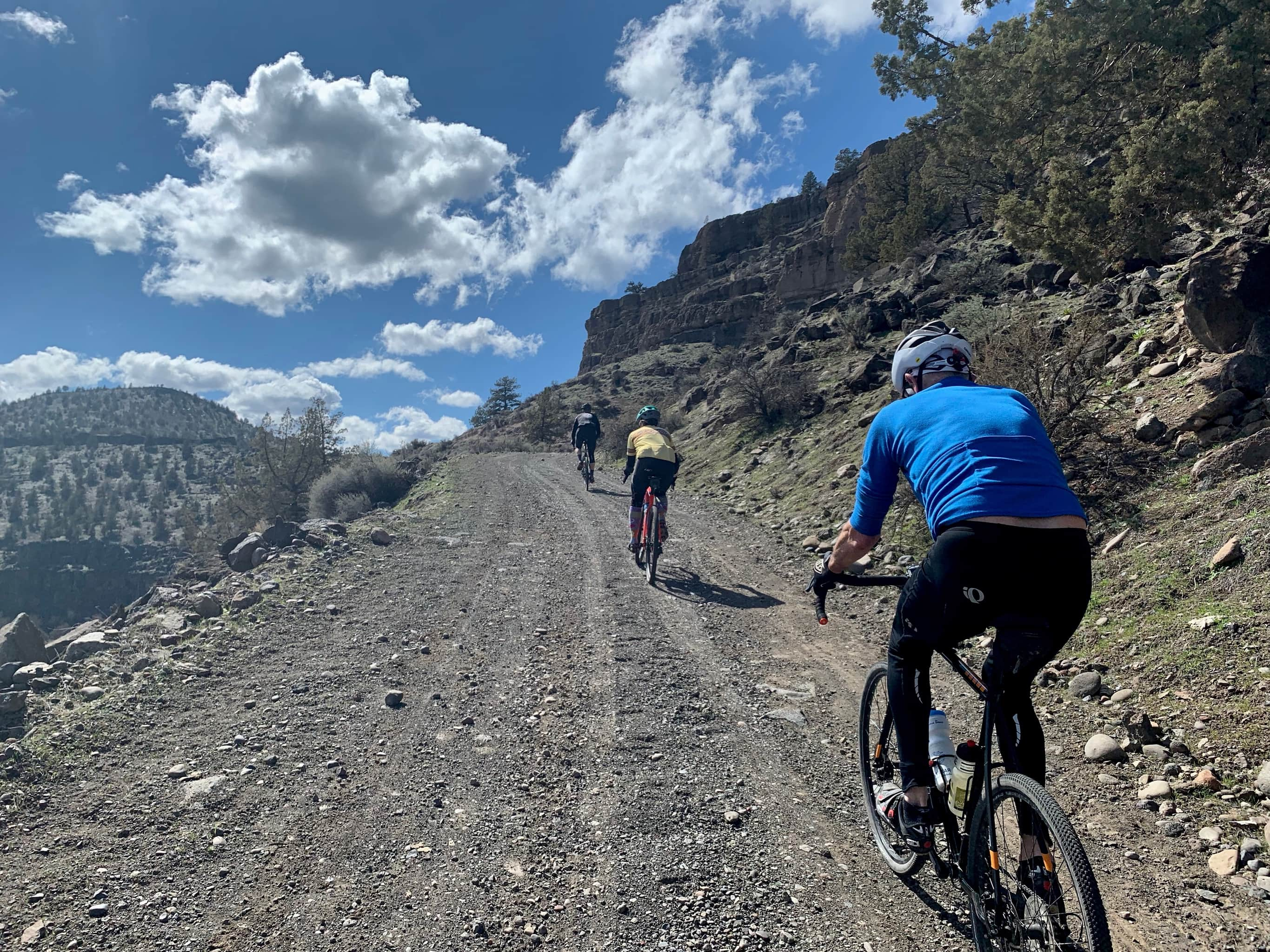 Cyclists climbing gravel road leading out from Lake Simtustus.