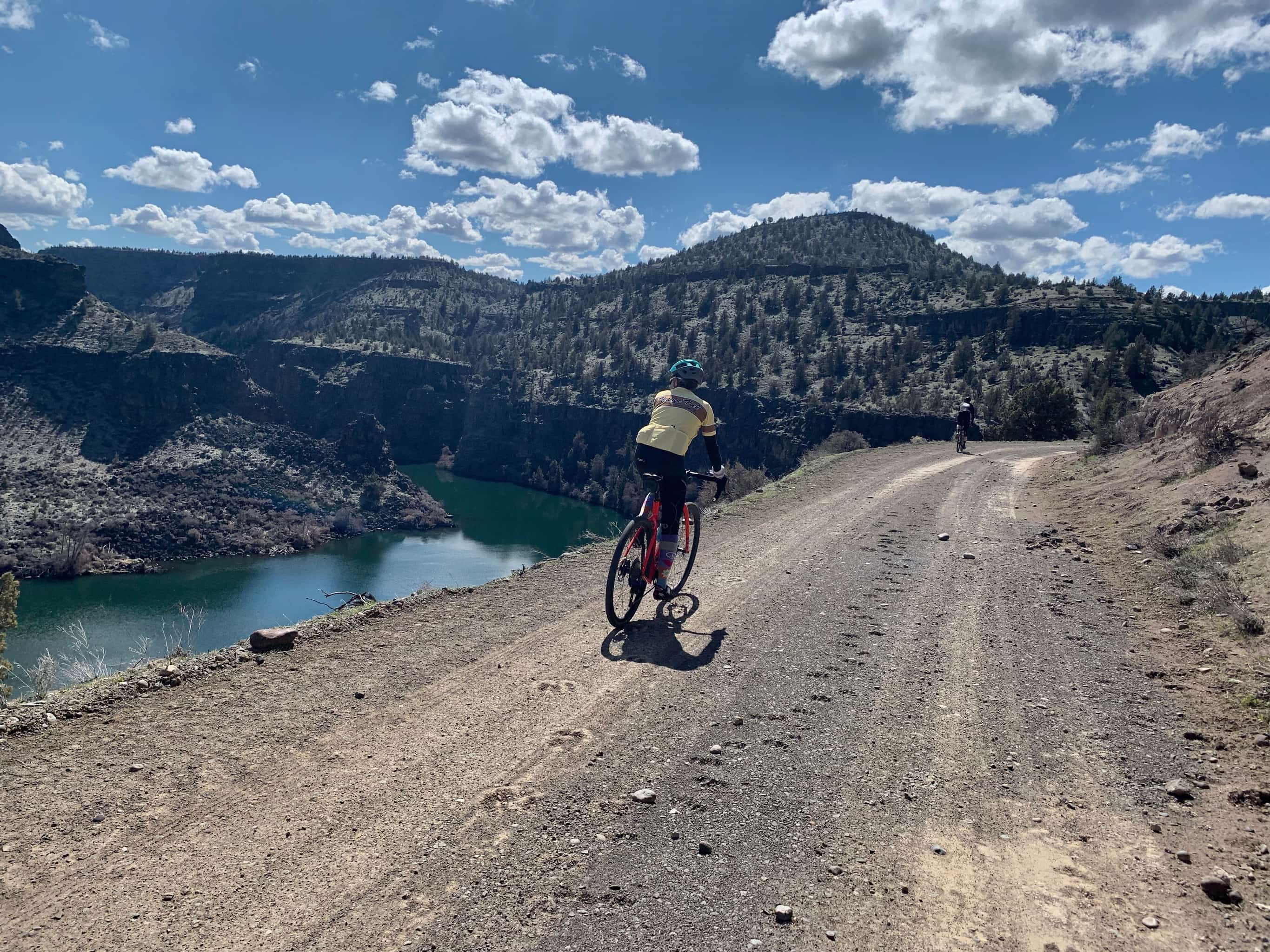 Cyclist on gravel road, flat, with views of Lake Simtustus to the left.