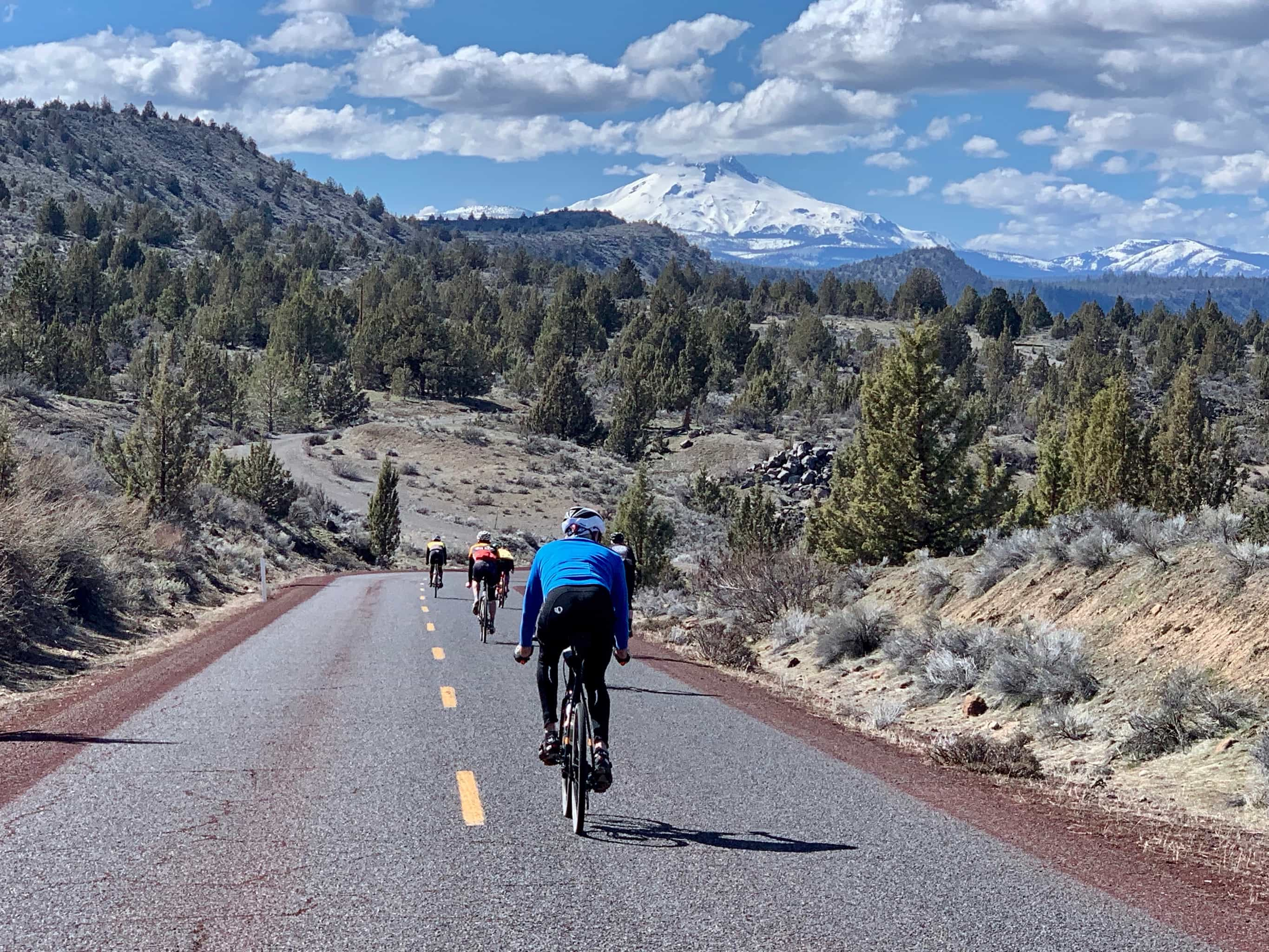 Cyclists on paved road descending with Mt. Jefferson in the background.