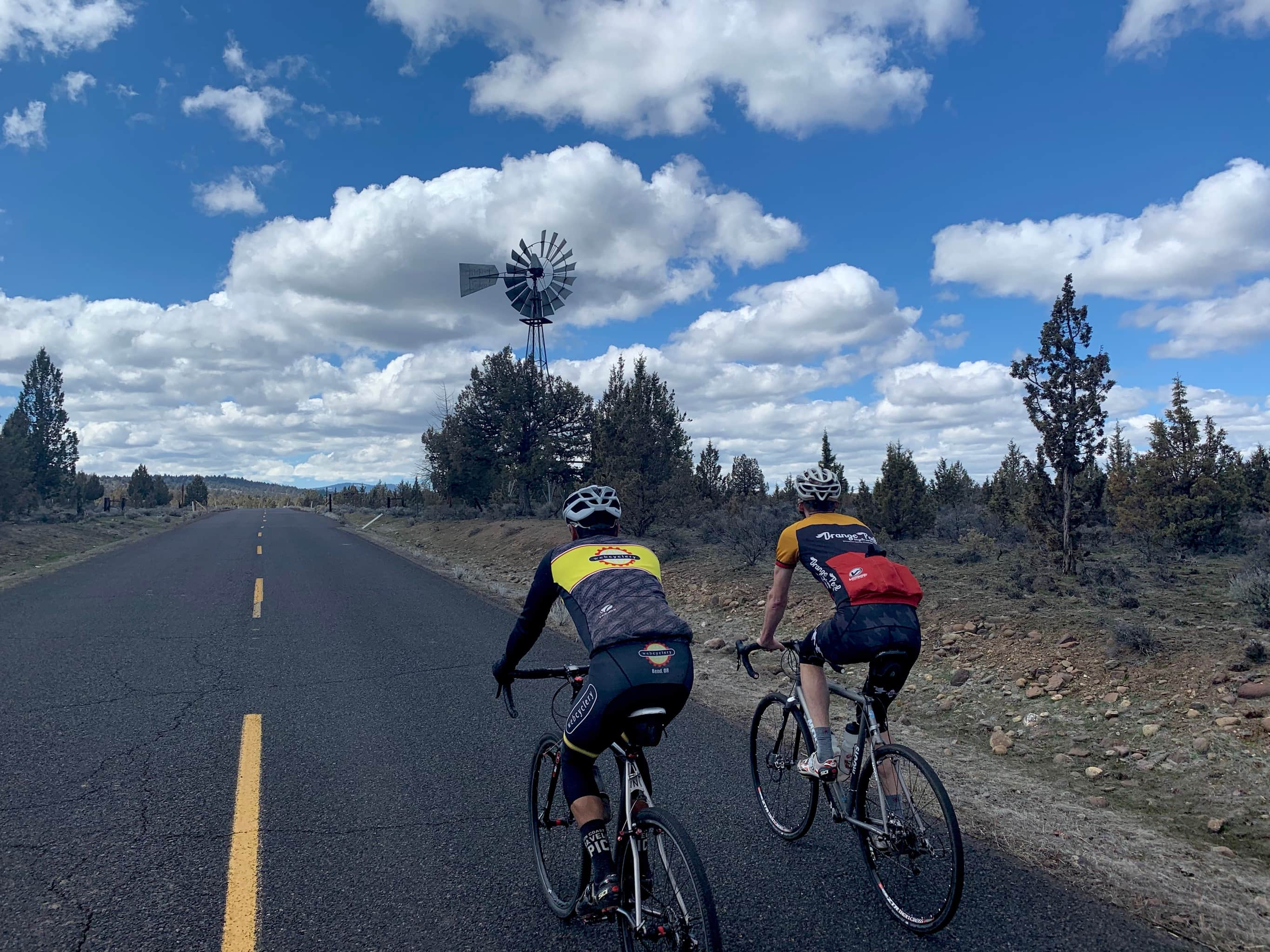 Cyclists on paved road with windmill in background.