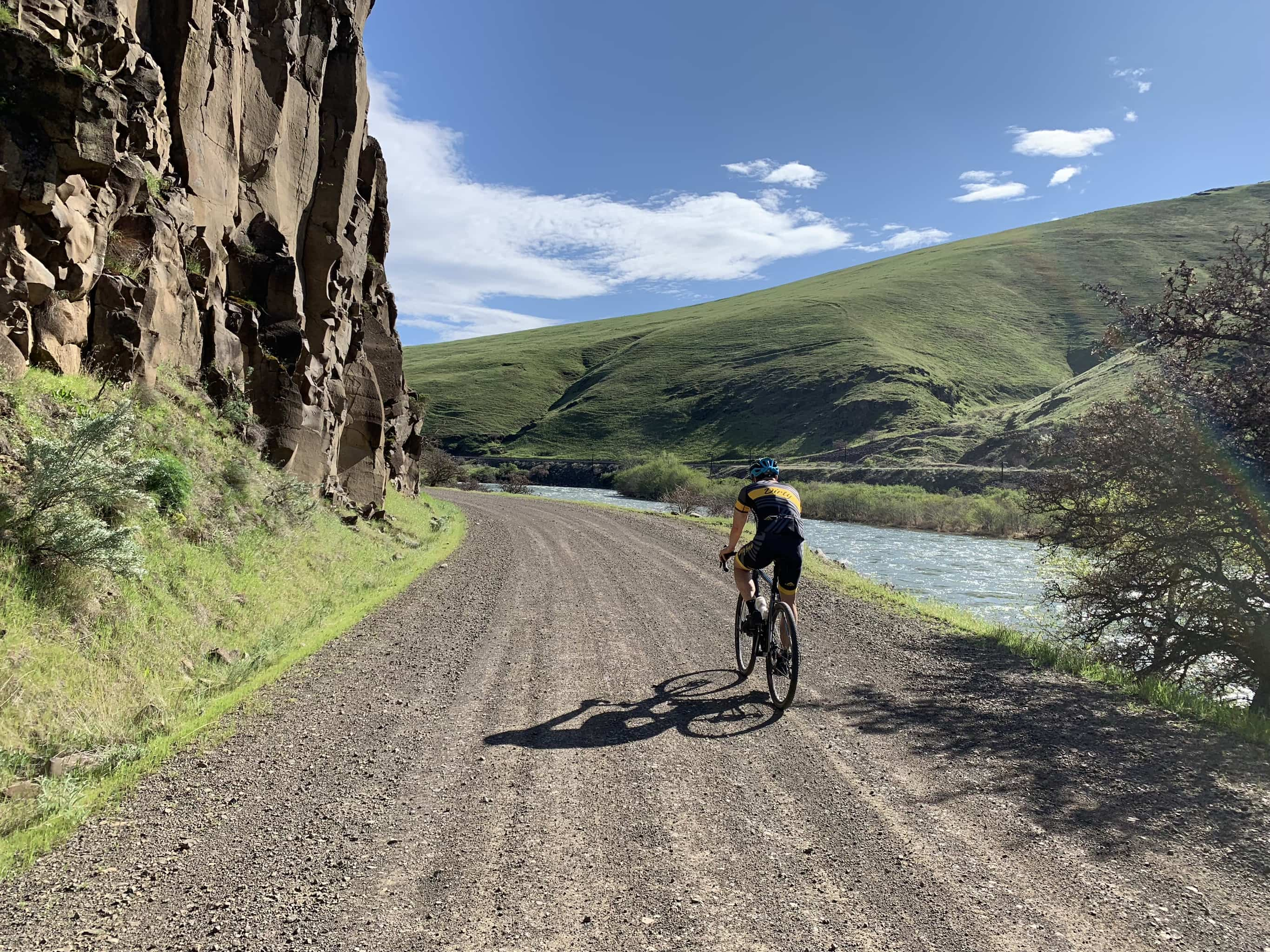 Bike rider on gravel road with basalt columns to left and Deschutes River to the right.