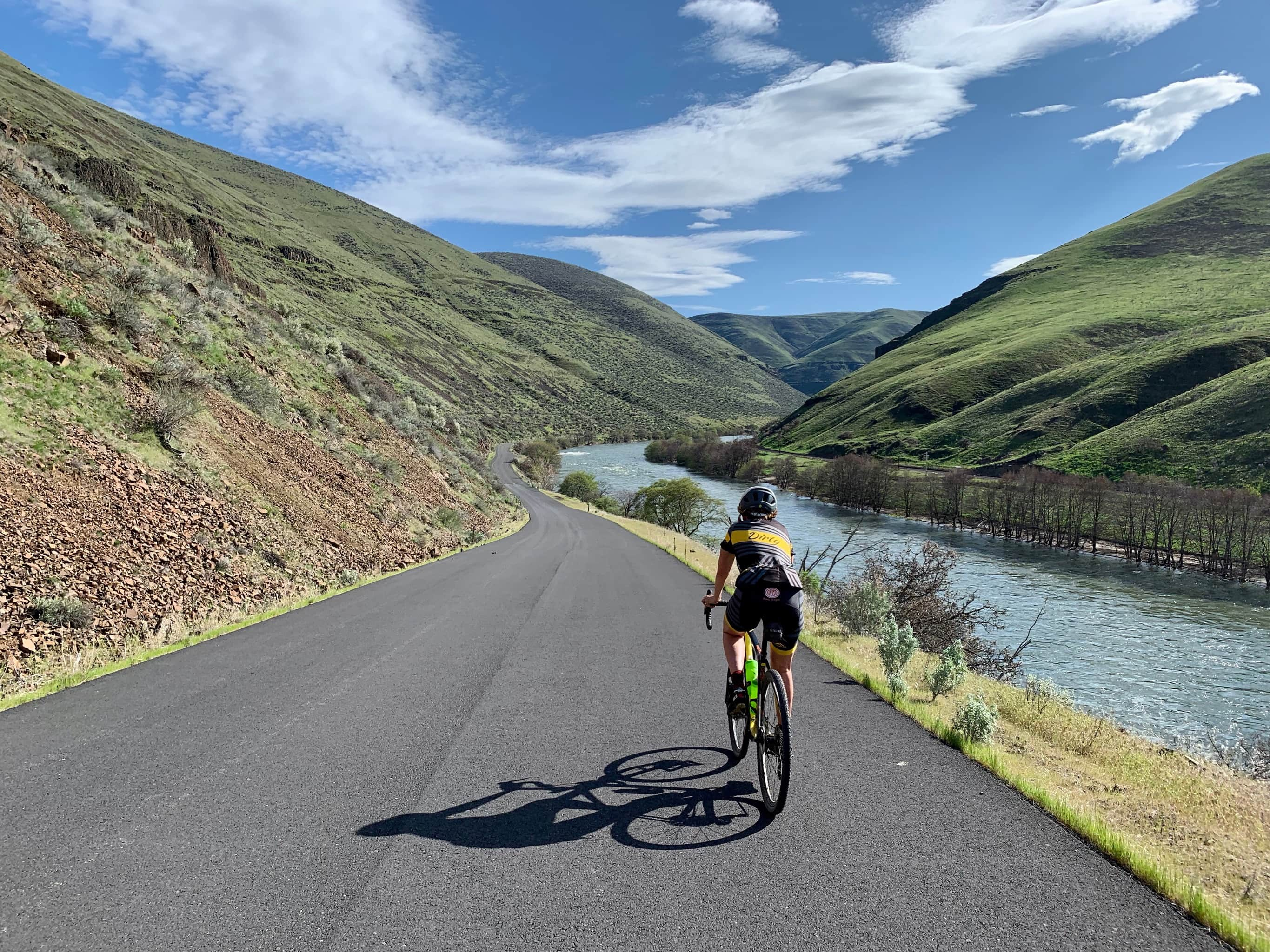 Bike rider on paved downhill, going south, along the Deschutes River near Maupin, Oregon.