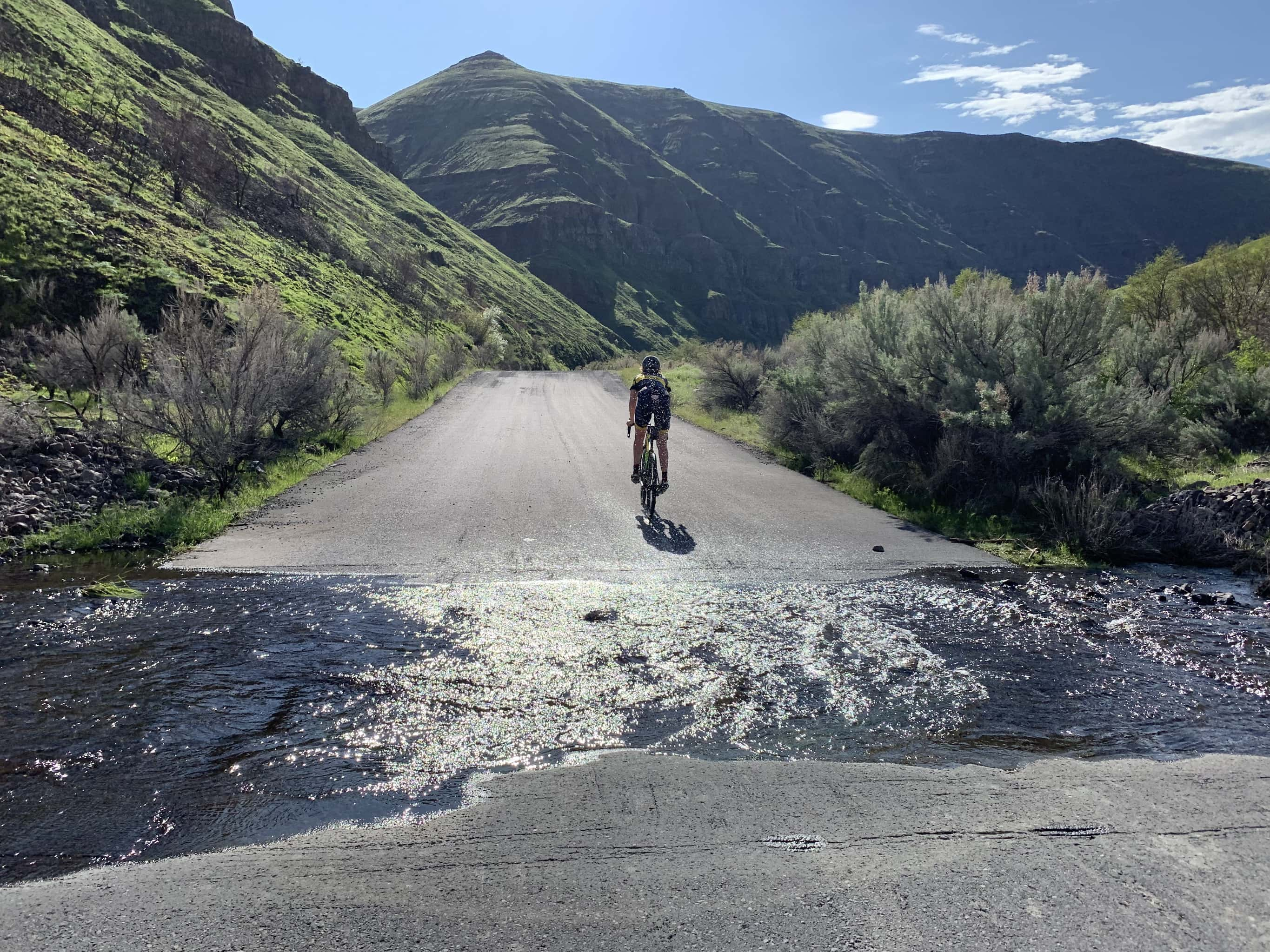Cyclist riding through small water crossing along the lower Deschutes River.