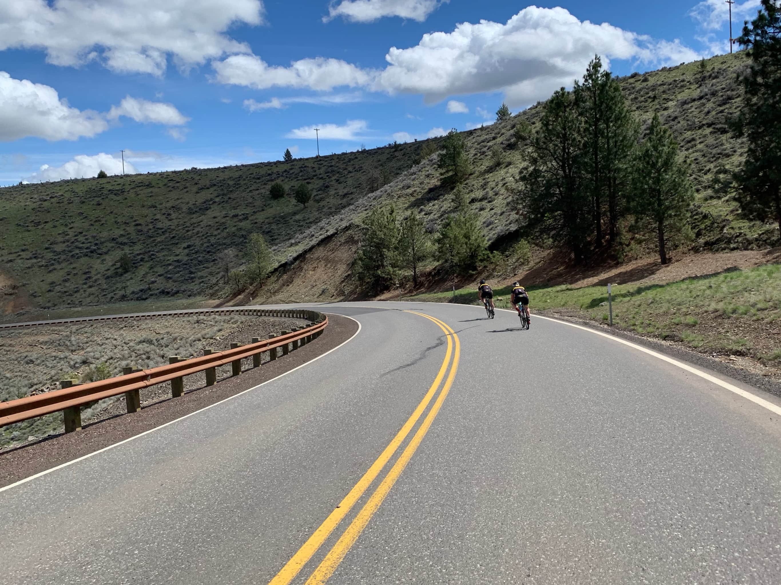 Bike riders on paved road descending into Tygh Valley.