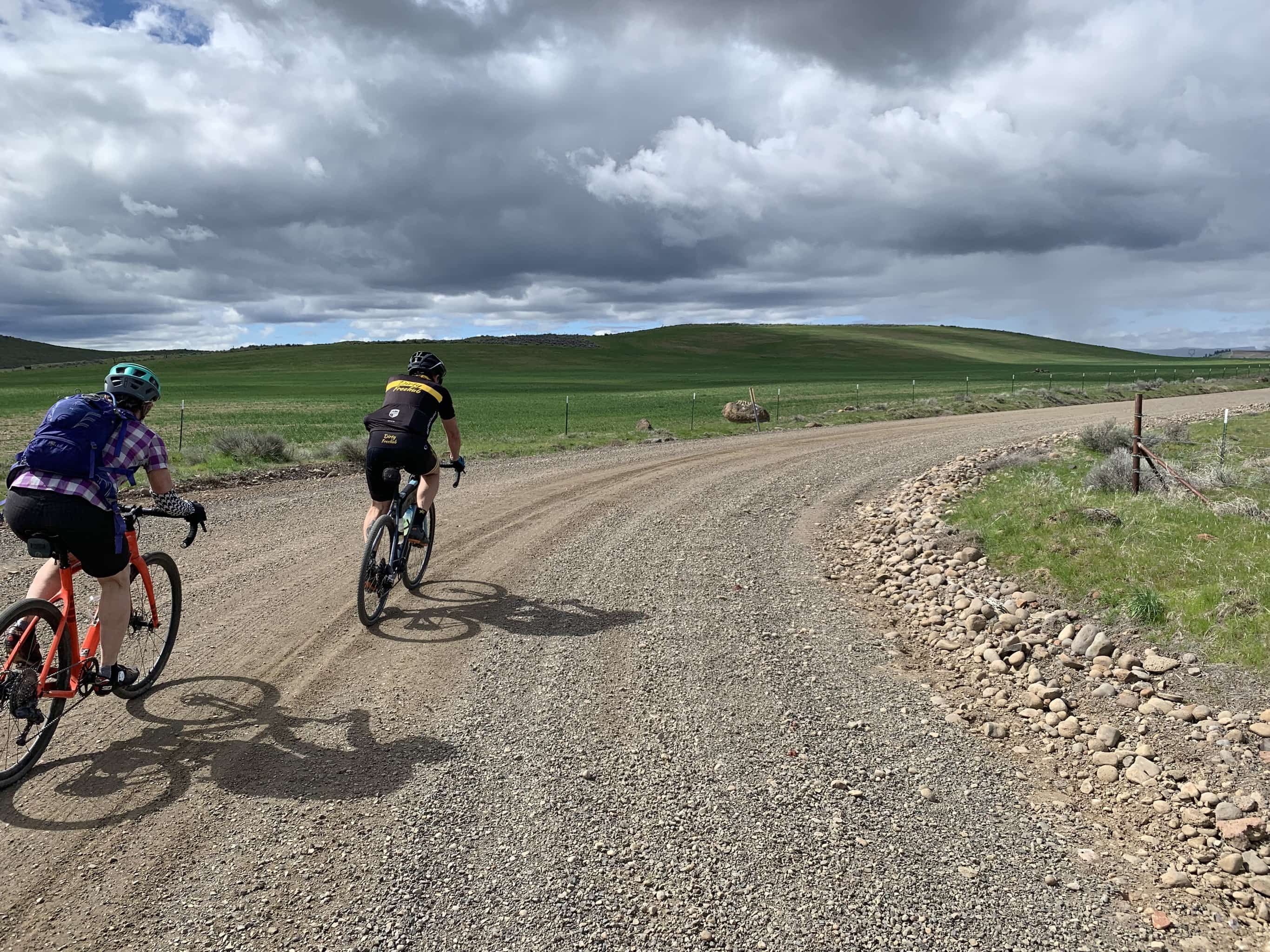 Gravel cyclist on sweeping turn on gravel road.