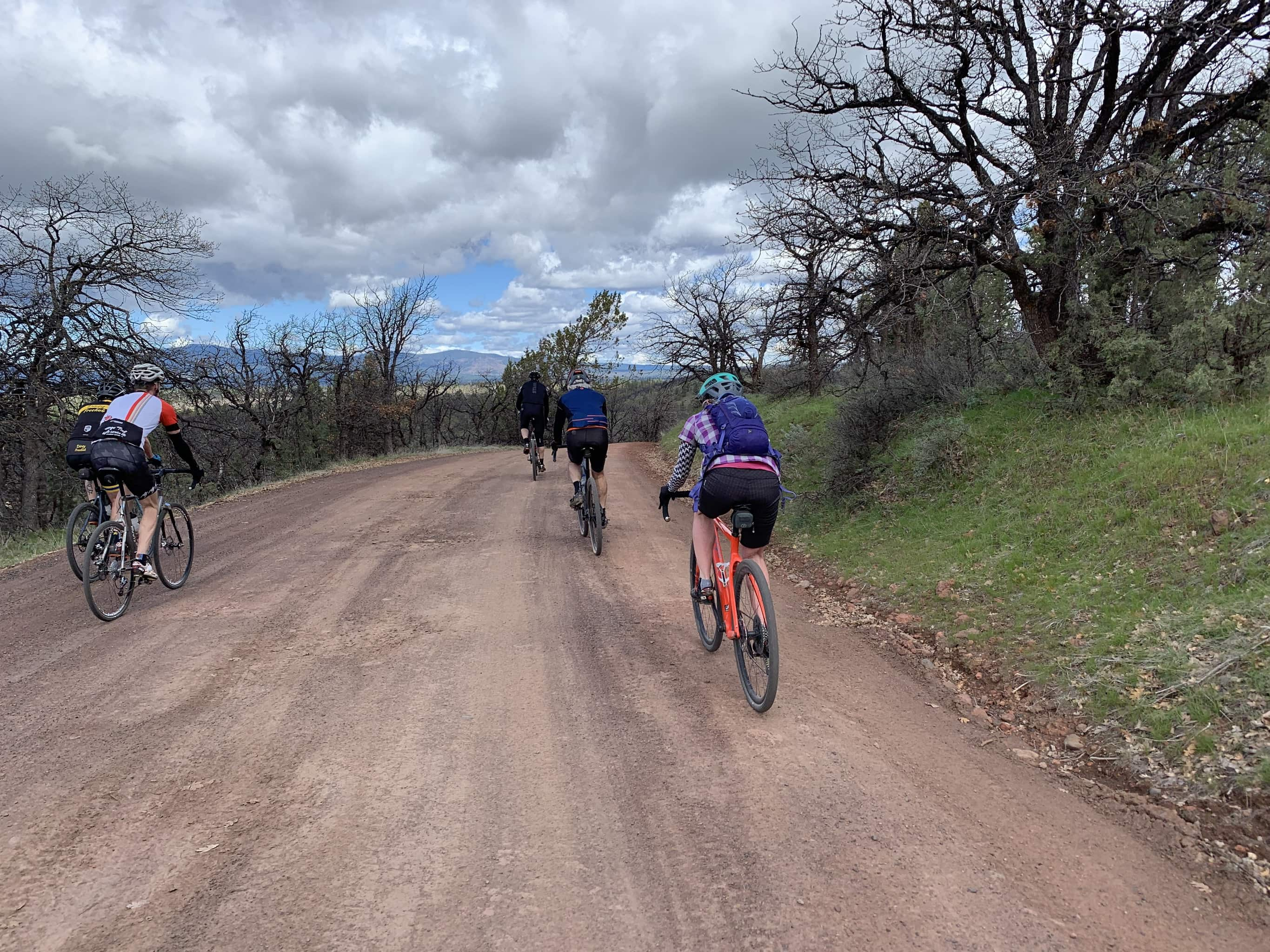 Cyclists on gravel road dropping into White River canyon.