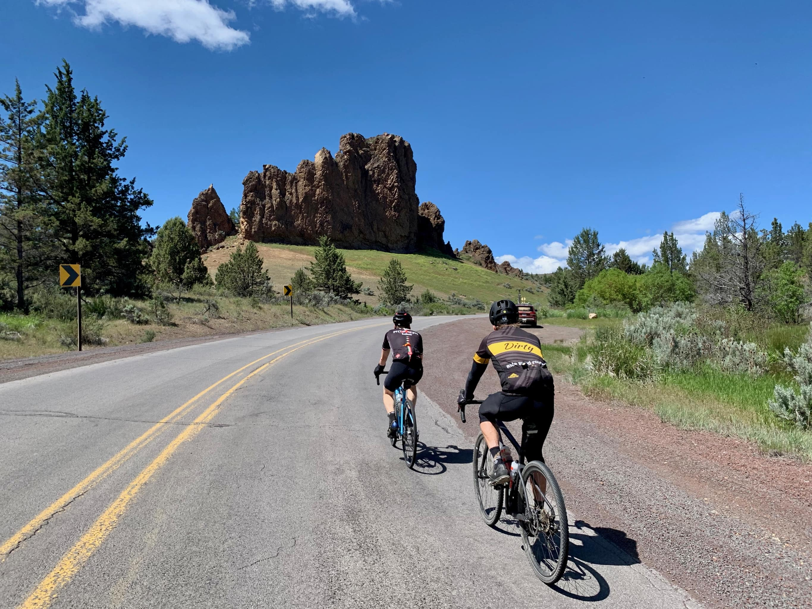 Cyclists on the SE Paulina Highway with rock monolith in the background.
