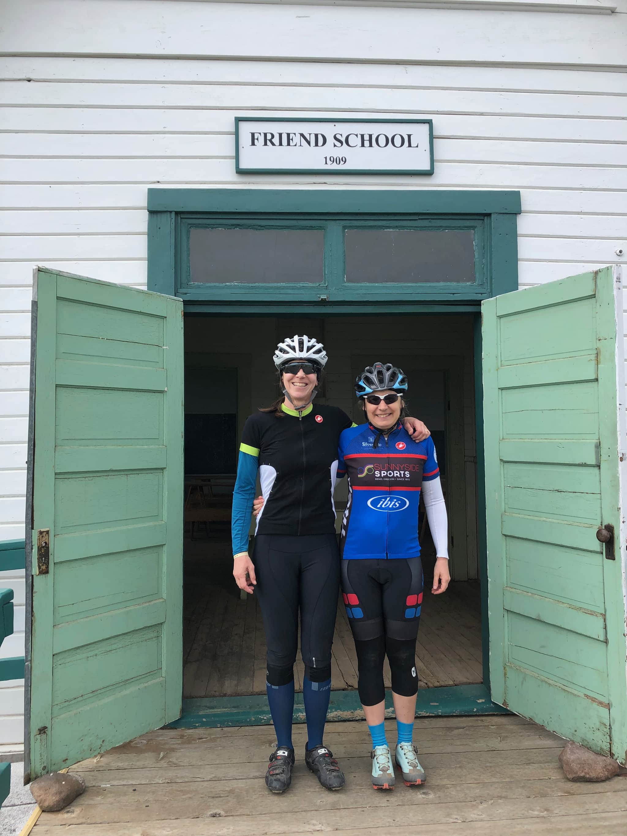 Two gravel girls standing in front of the historic Friend schoolhouse.