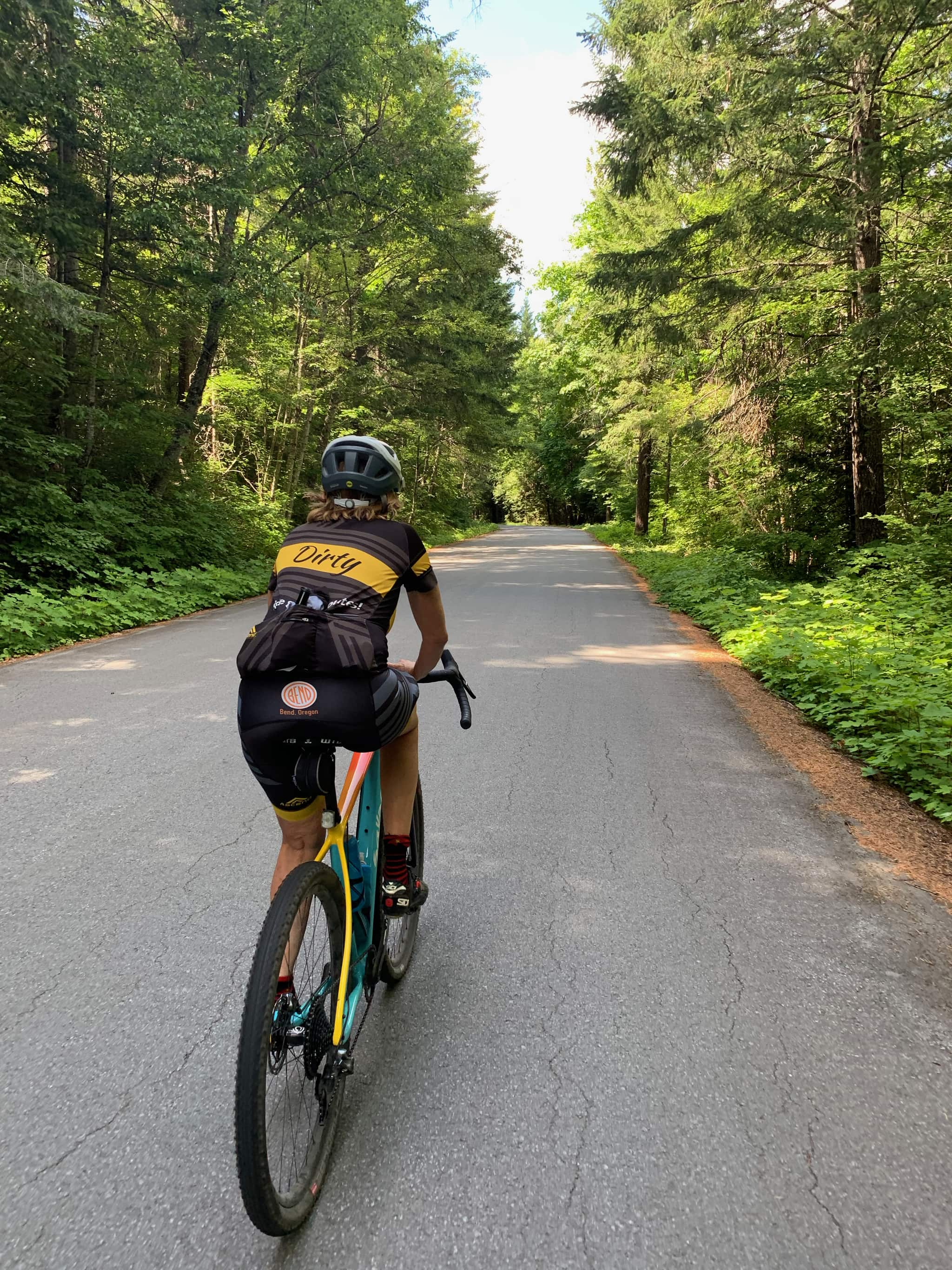 Cyclist on paved forest service road in Gifford Pinchot National Forest near Trout Lake.