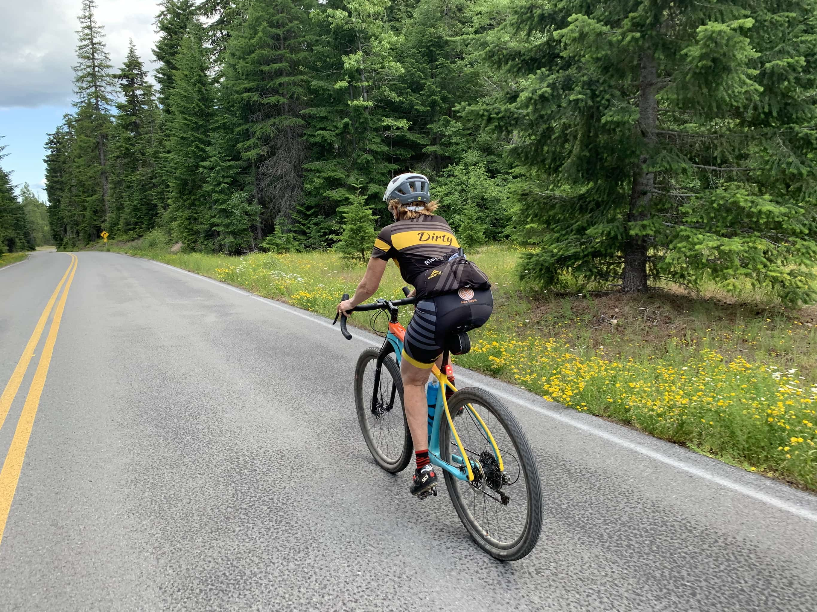 Bike rider on NF-22 with yellow flowers in the background north of White Salmon, WA.