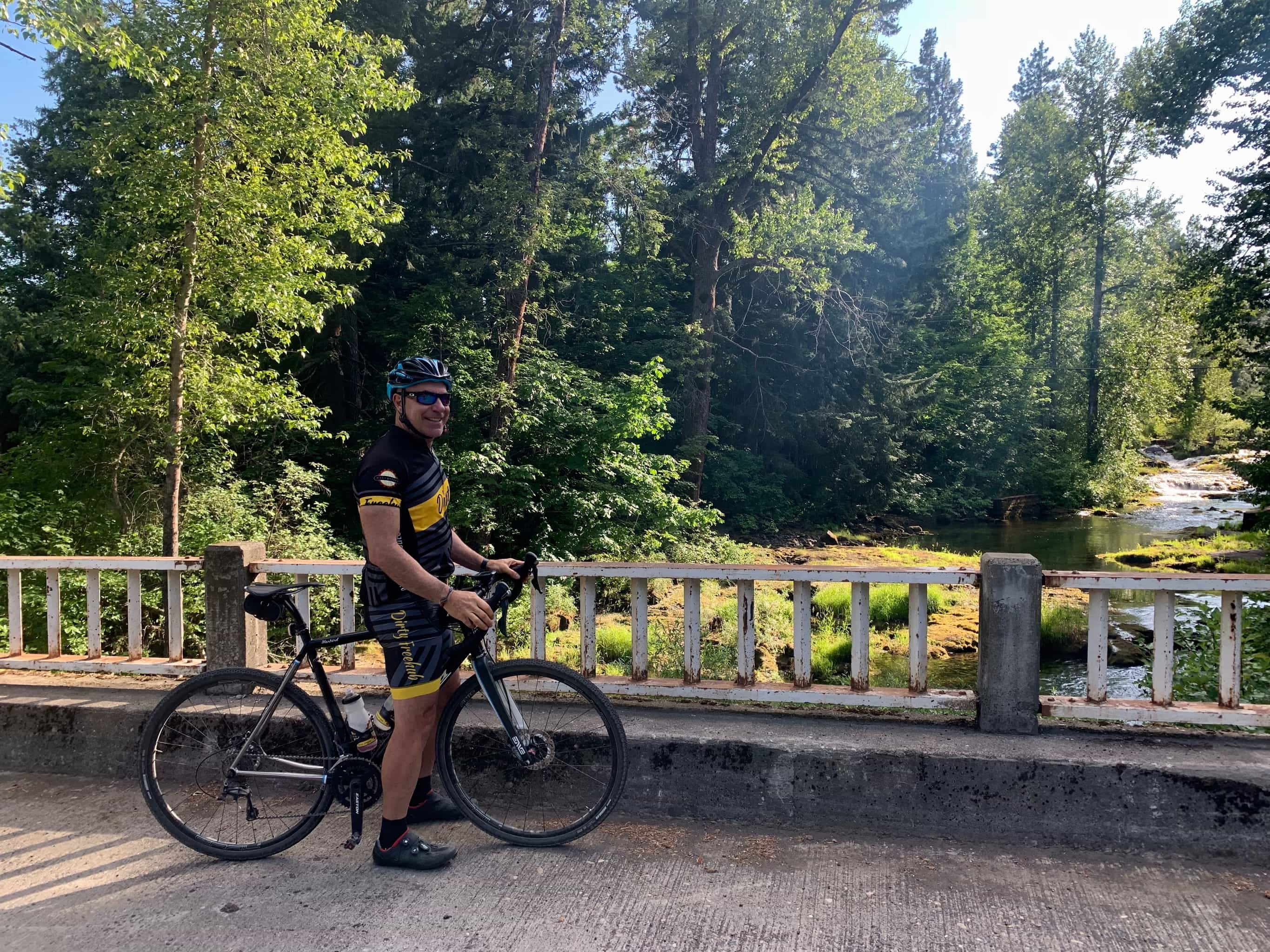 Cyclist standing on bridge in front of Trout Lake Creek near Gifford Pinchot National Forest on NF-23.