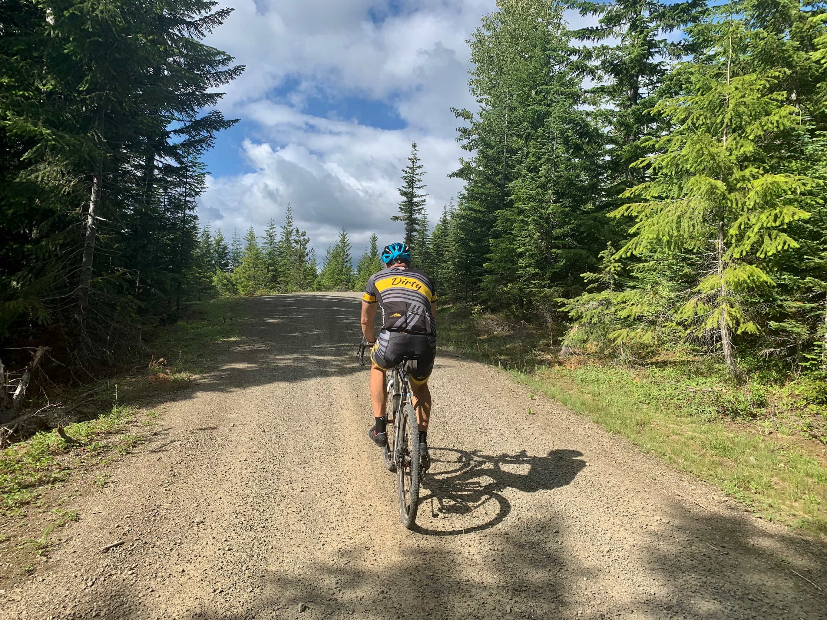 Bike rider on gravel road nearing intersection of NF-8810 and NF-8860 in Gifford Pinchot National Forest.