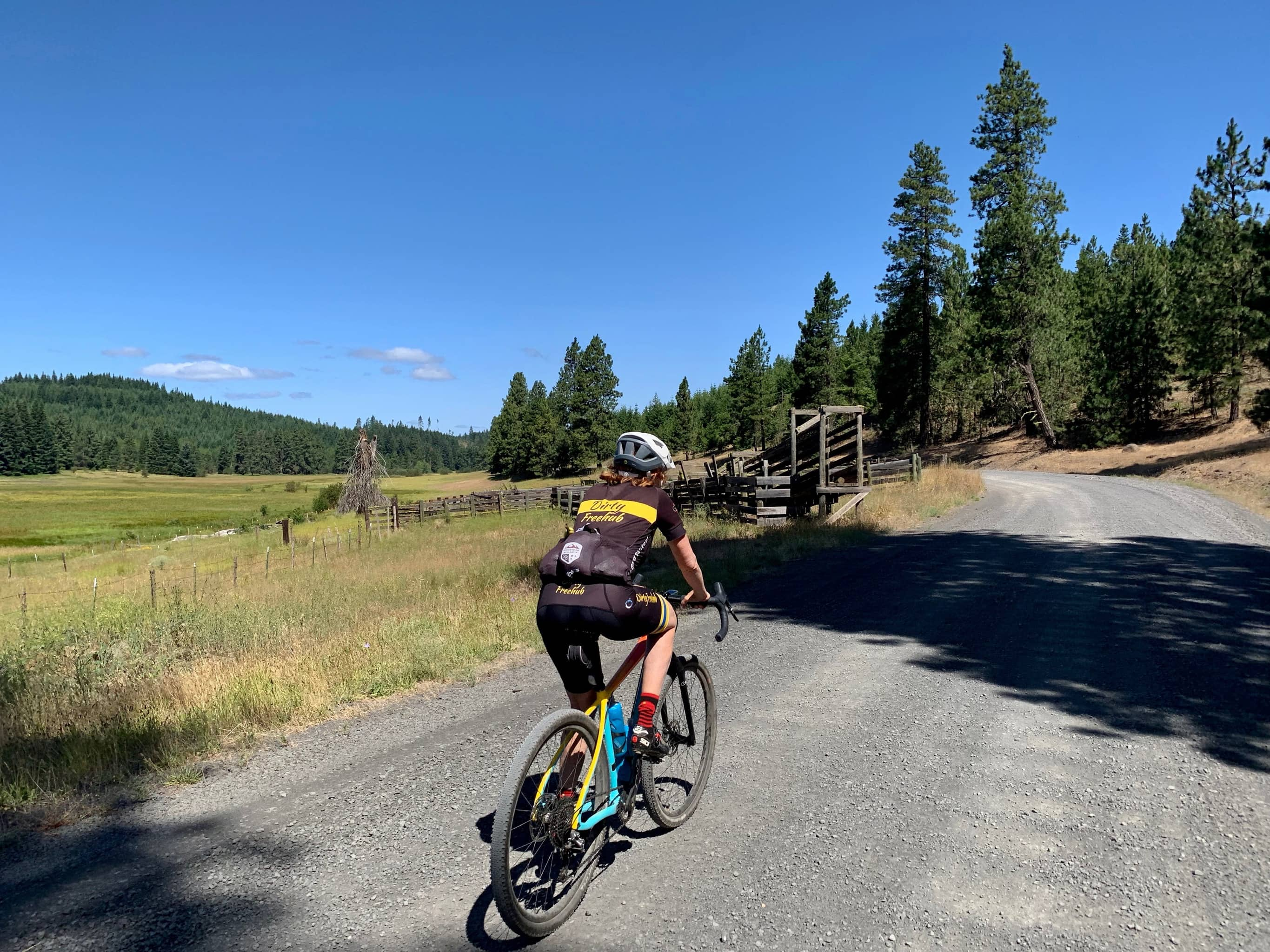 Bike rider on gravel road with cattle corral in Washington state.