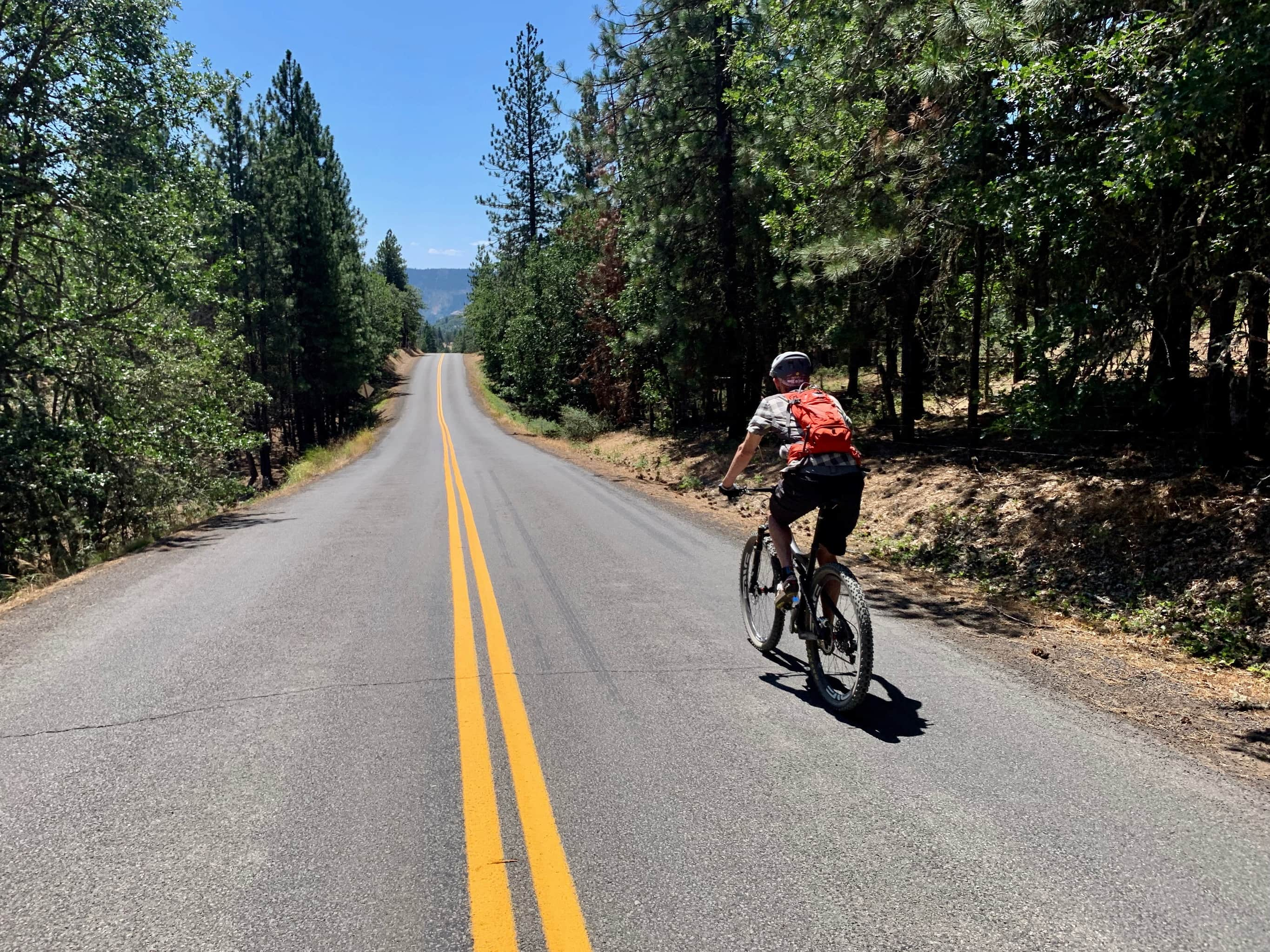 Cyclist descending the paved portion of the Lyle Snowden road north of the Columbia river.