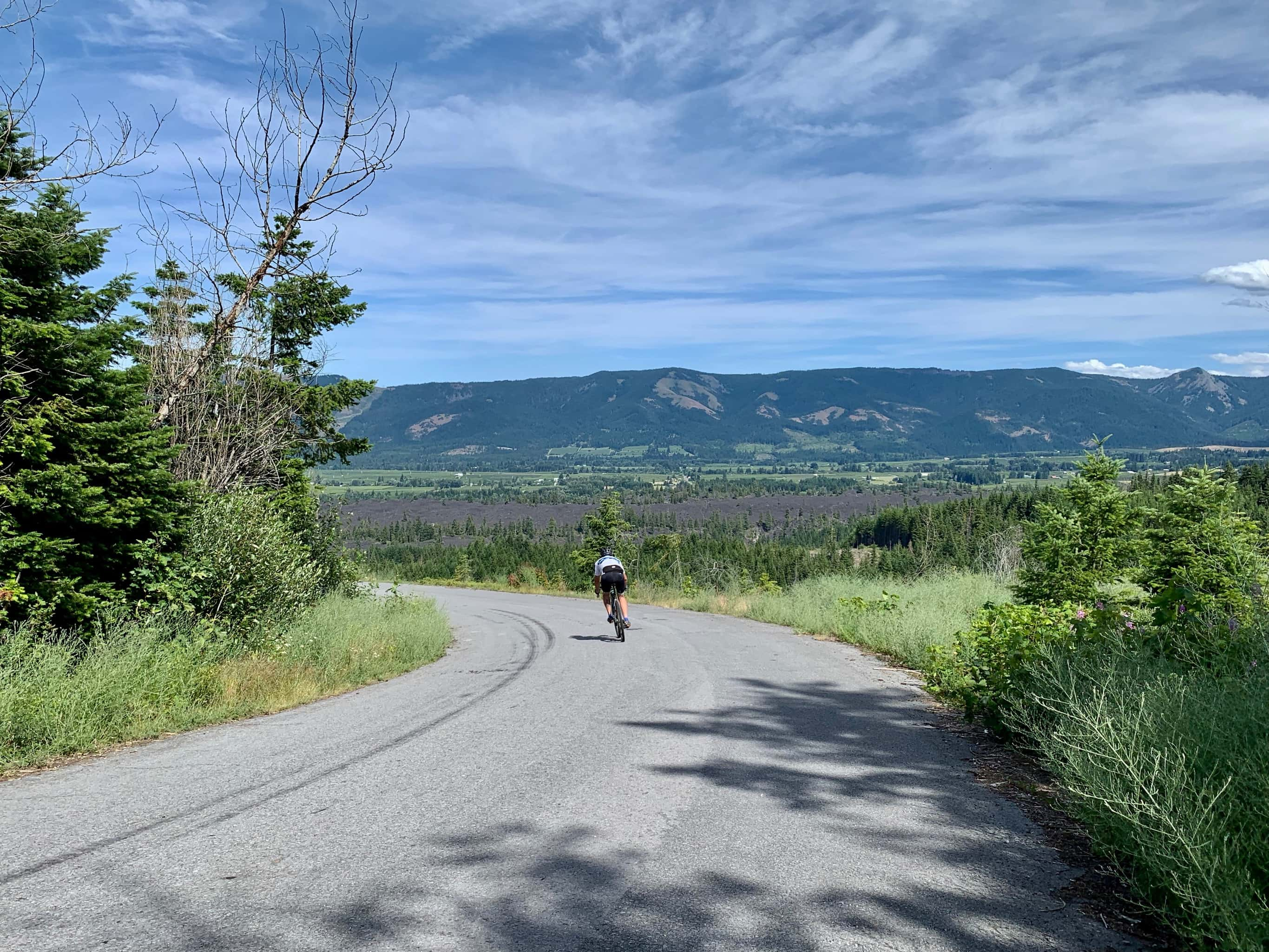 Cyclist descending Red Hill road with Parkdale lava flow in background.